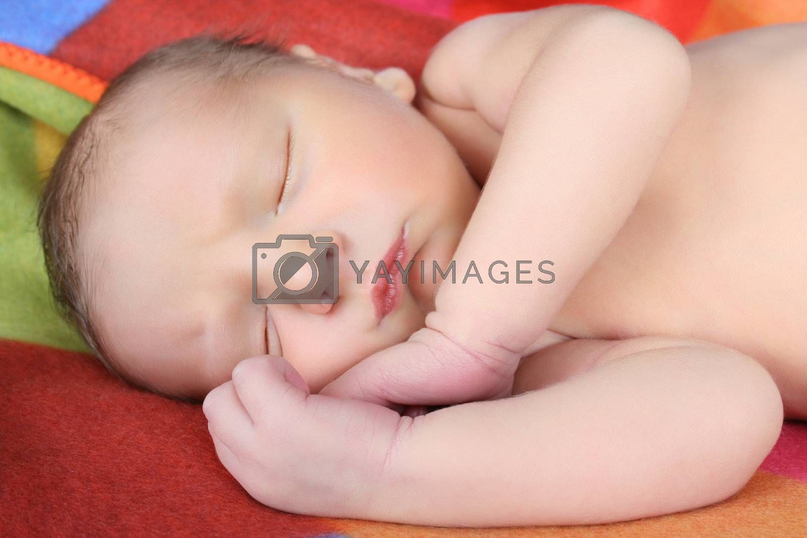 Newborn baby boy lying on a colorful blanket