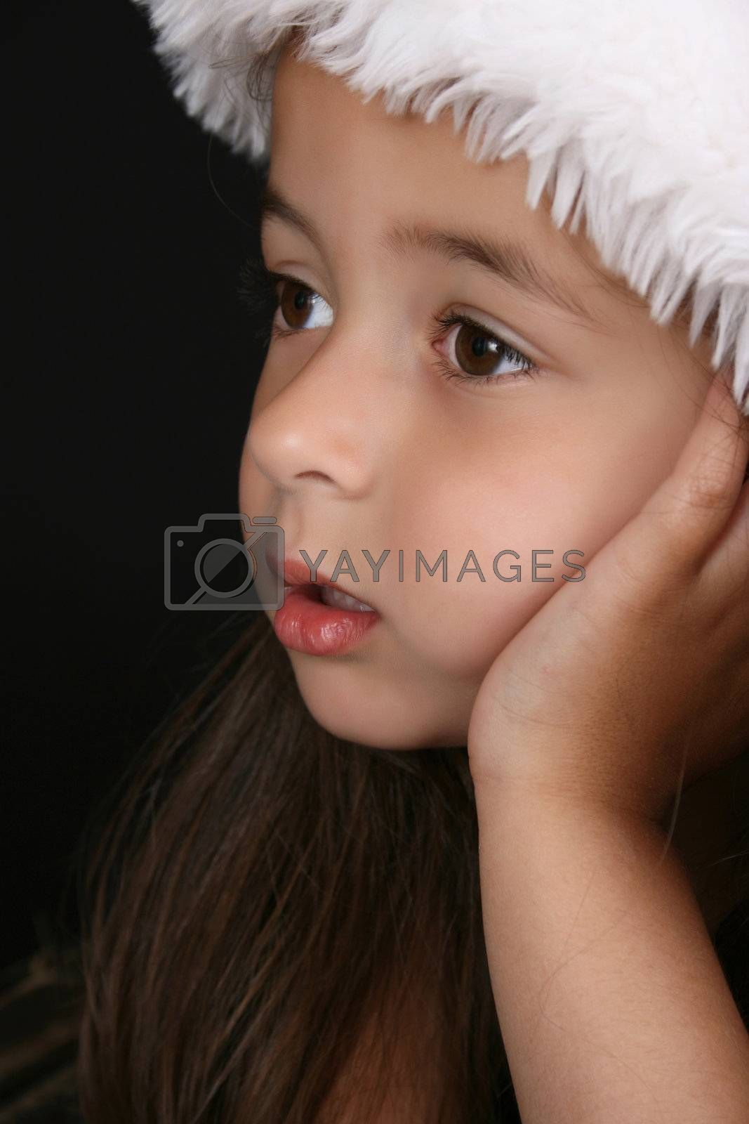 Cute little brunette girl wearing a christmas hat