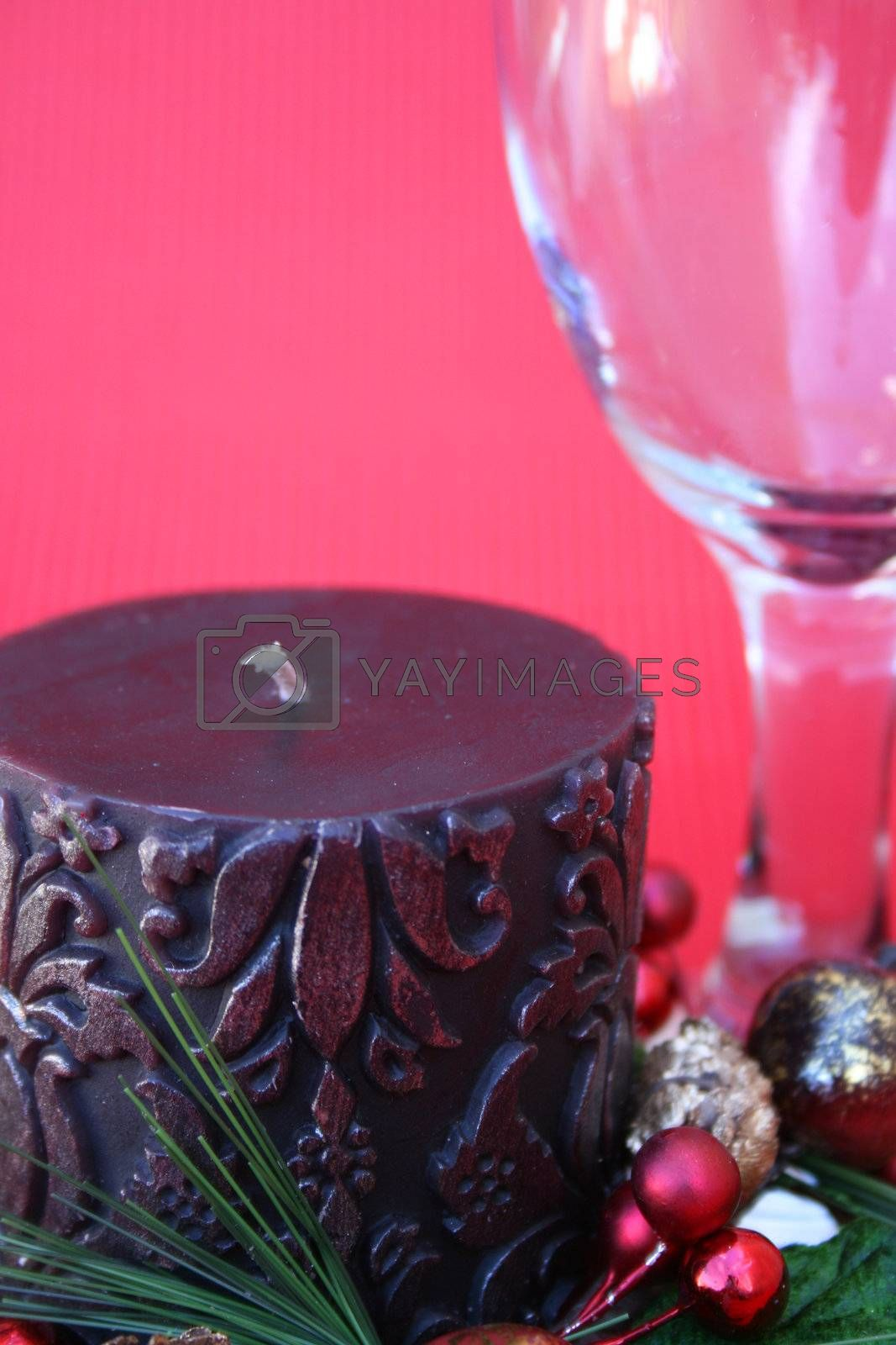 Dark candle with a christmas wreath and a wine glass on a red background