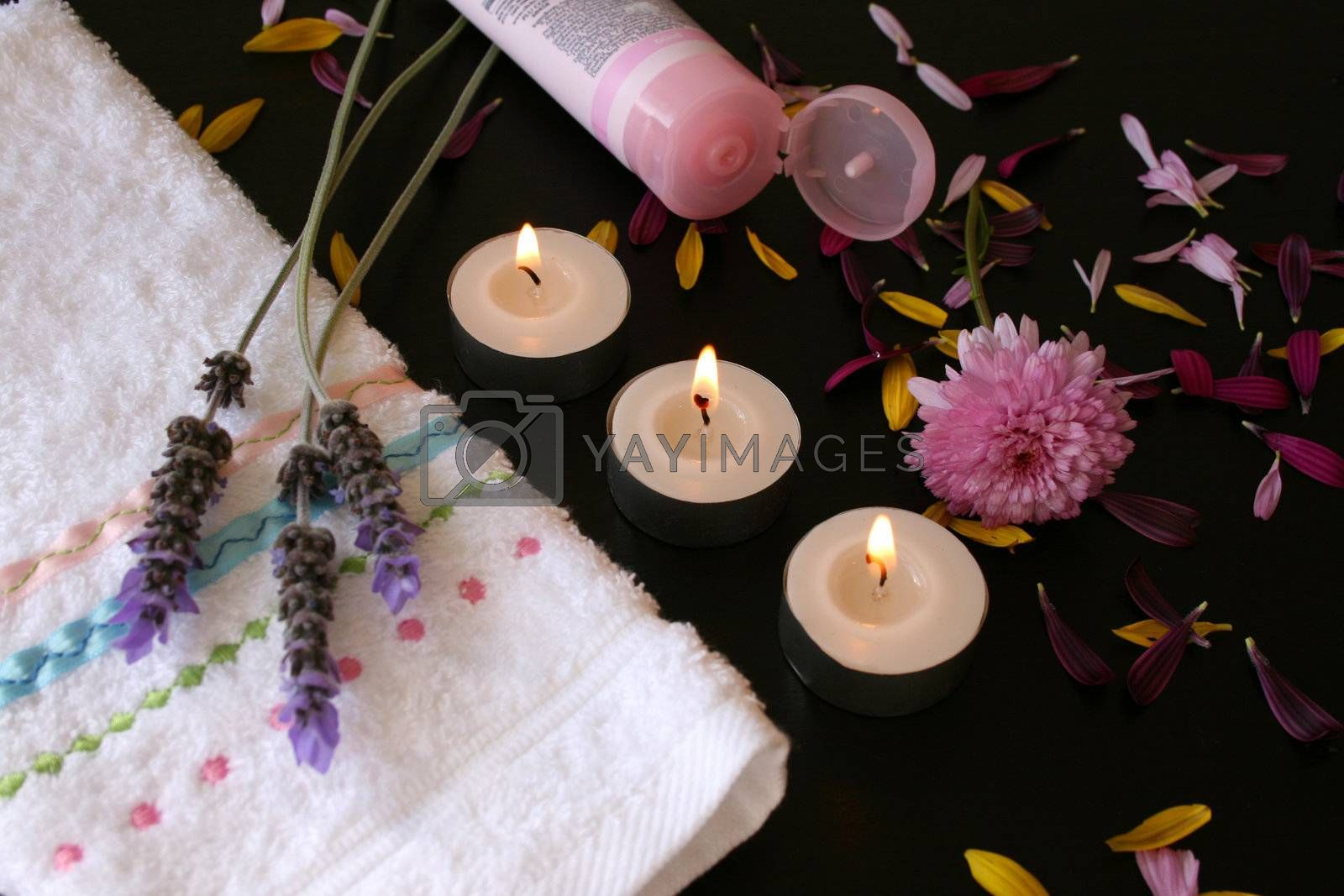 Pink body lotion in a tube next to a hand towel and candles