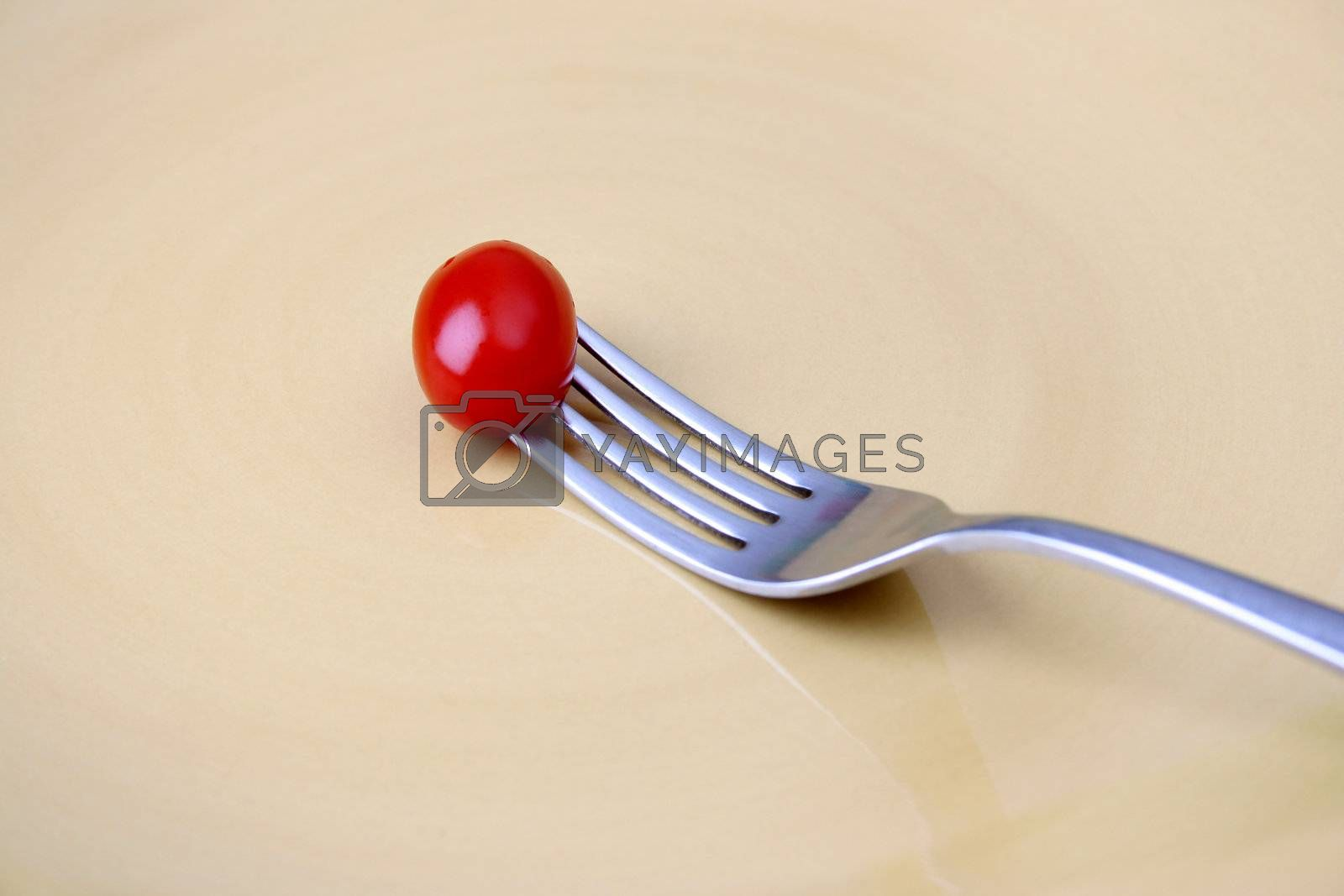 Single tomato on a fork against a yellow plate