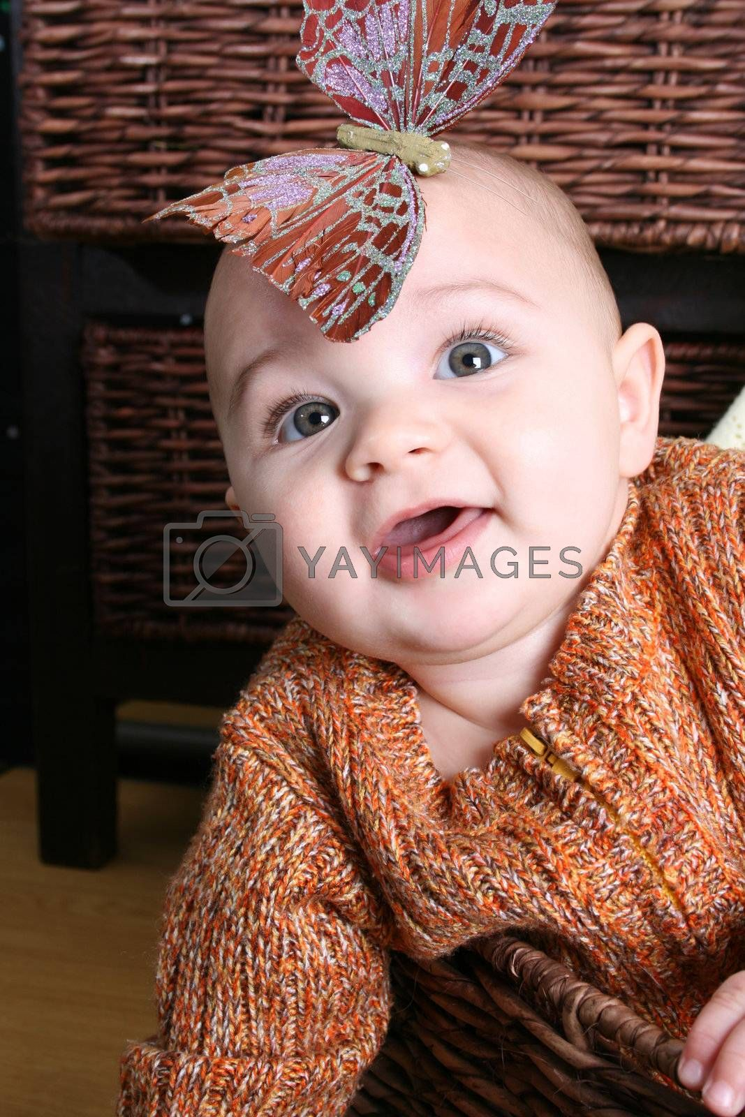 Six month old baby sitting infront of wooden drawers