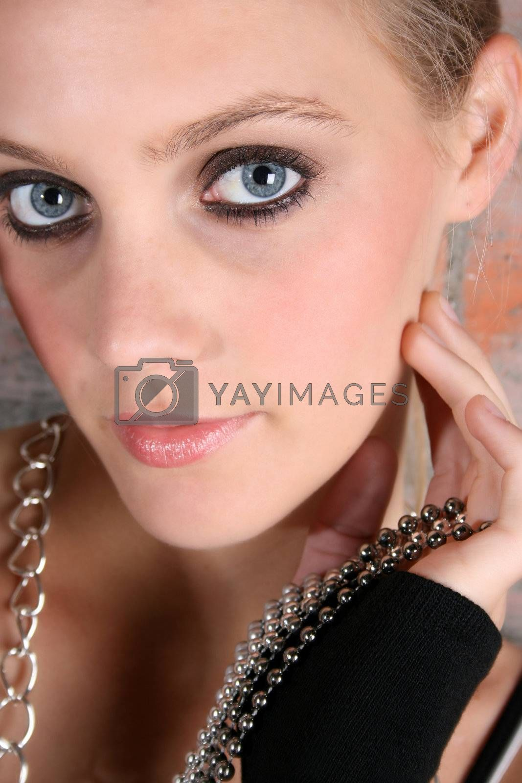Beautiful model with blue eyes holding strings of beads