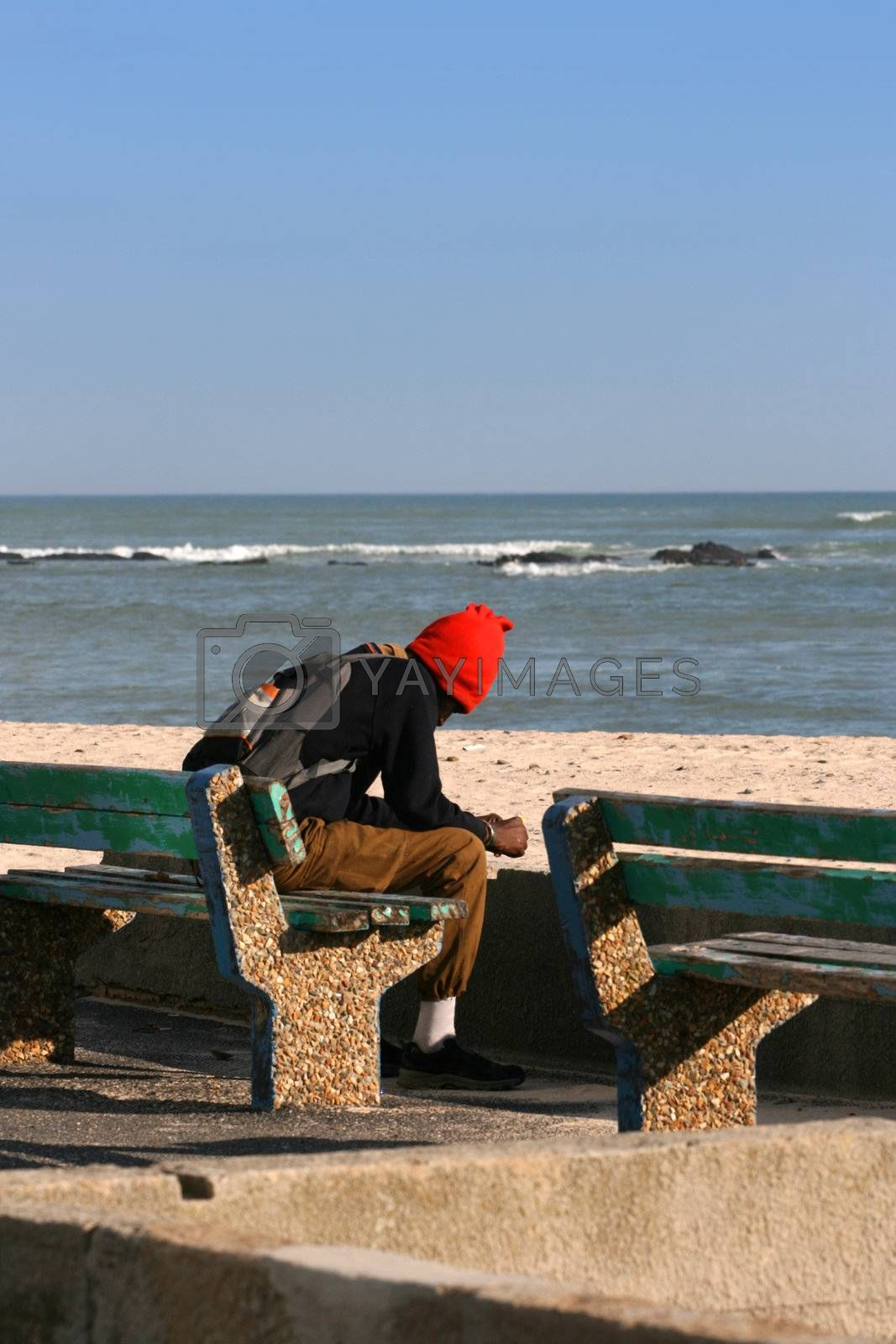 Lonely man sitting on a bench near the sea