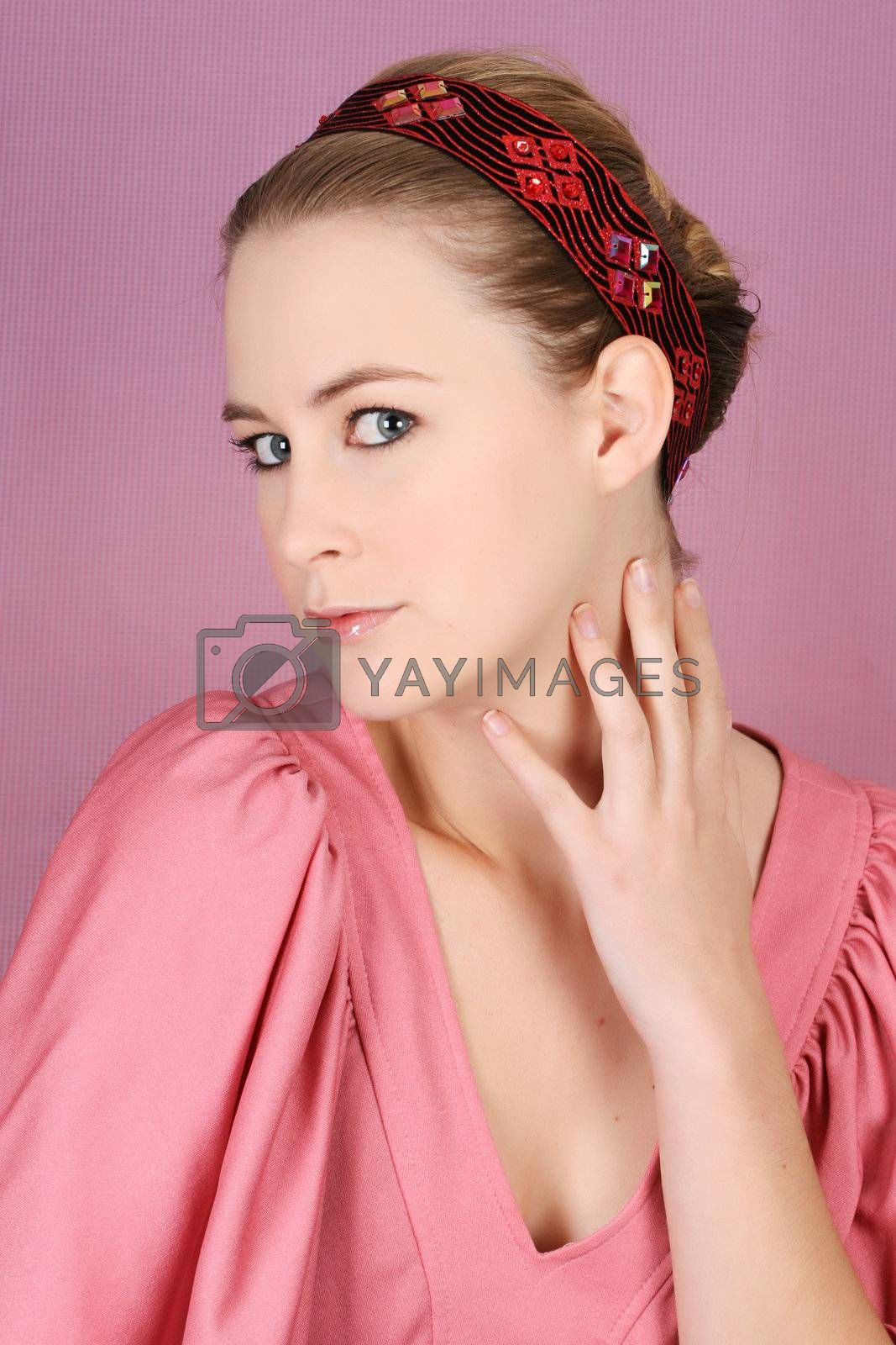 Beautiful blond female model wearing pink dress and hair accessories