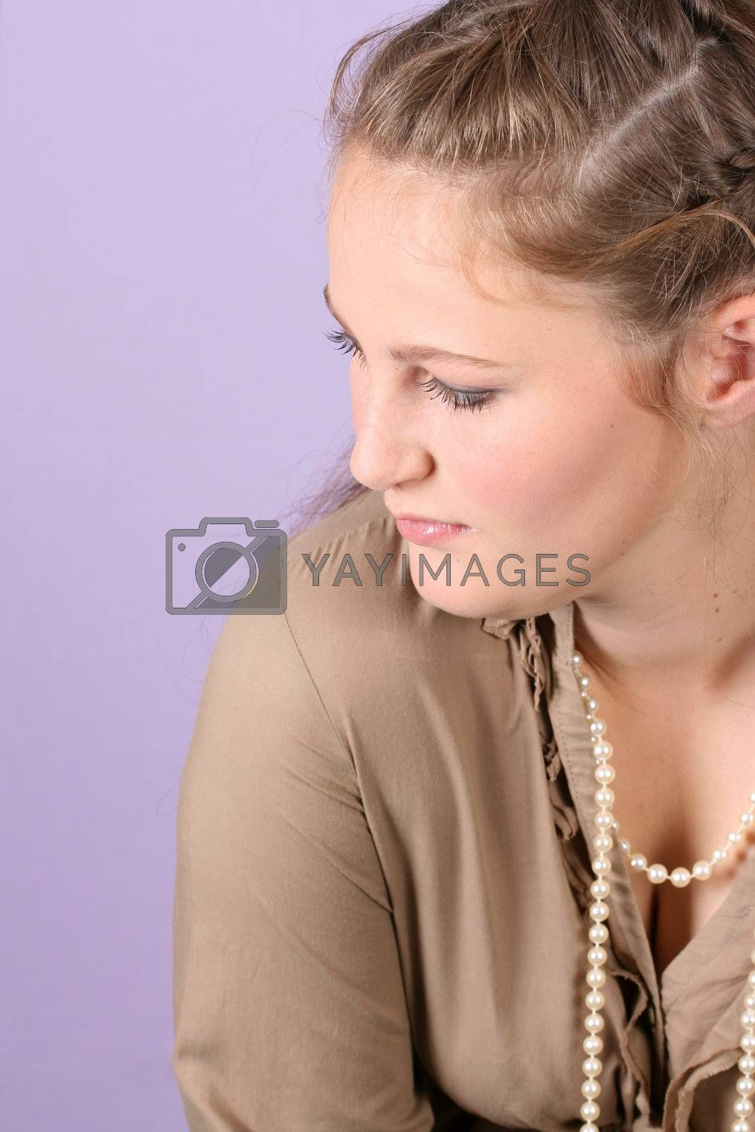 Beautiful teenage female against purple background, wearing pearls