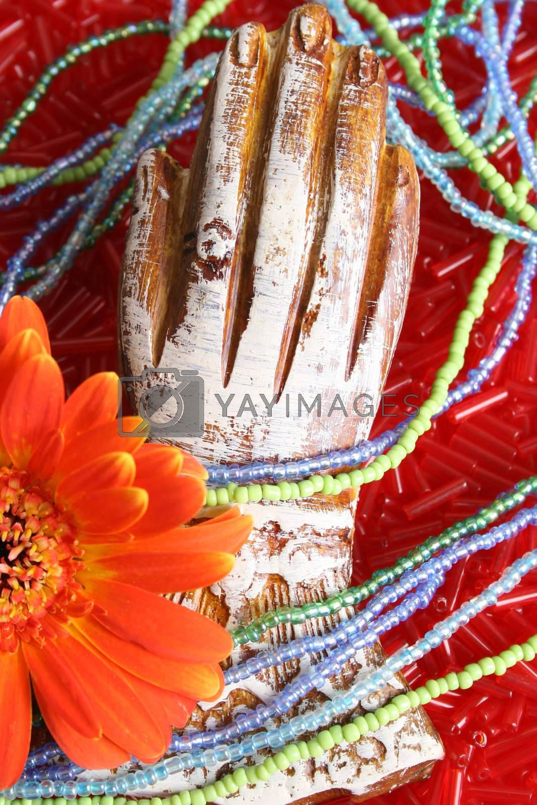 Wooden hand with beads and an orange flower