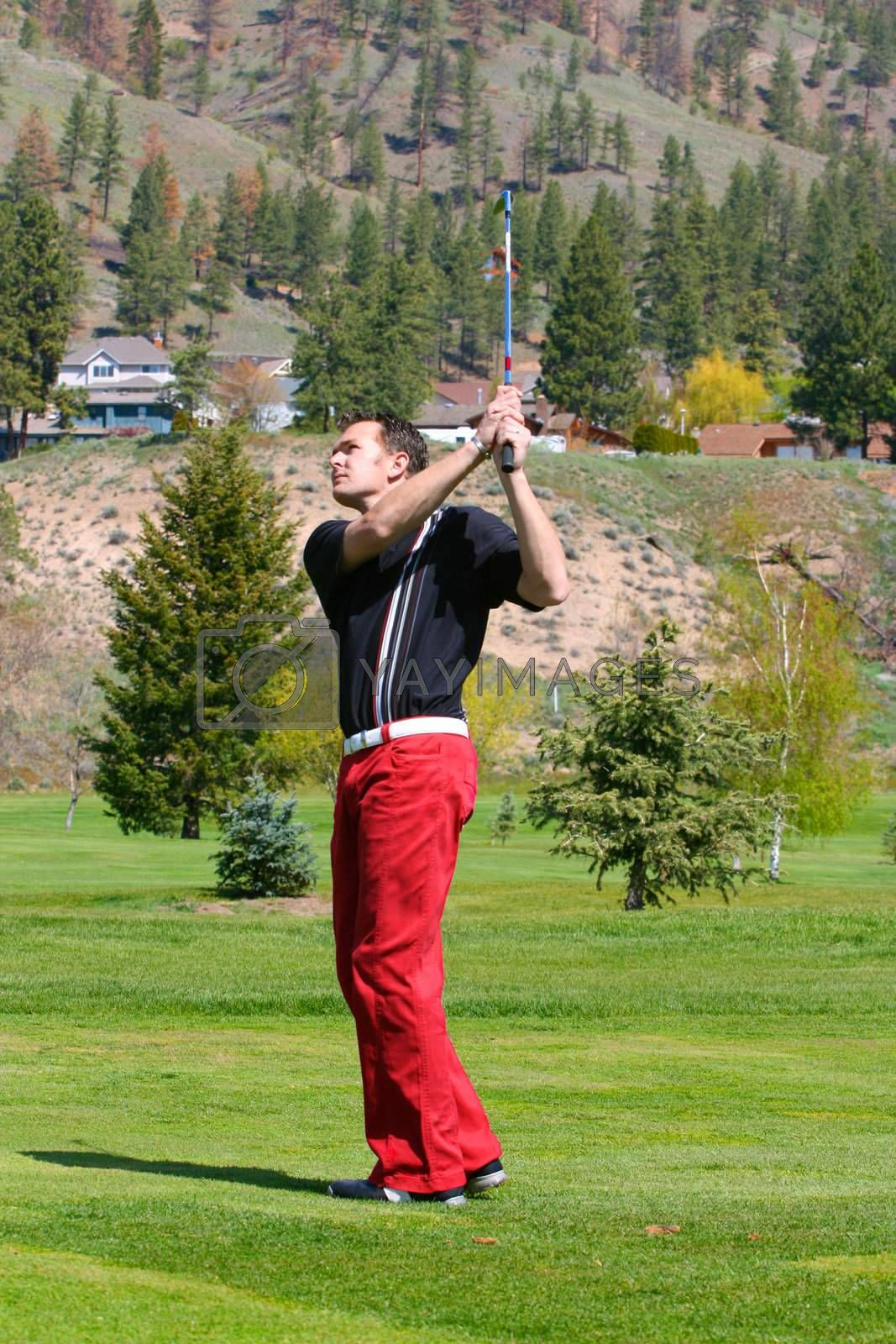 Young golfer following his ball after a shot from the fairway