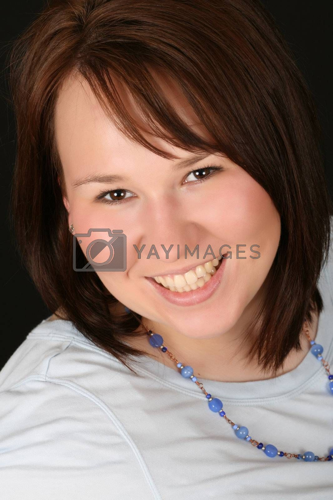 Headshot of beautiful brunette female on a black background