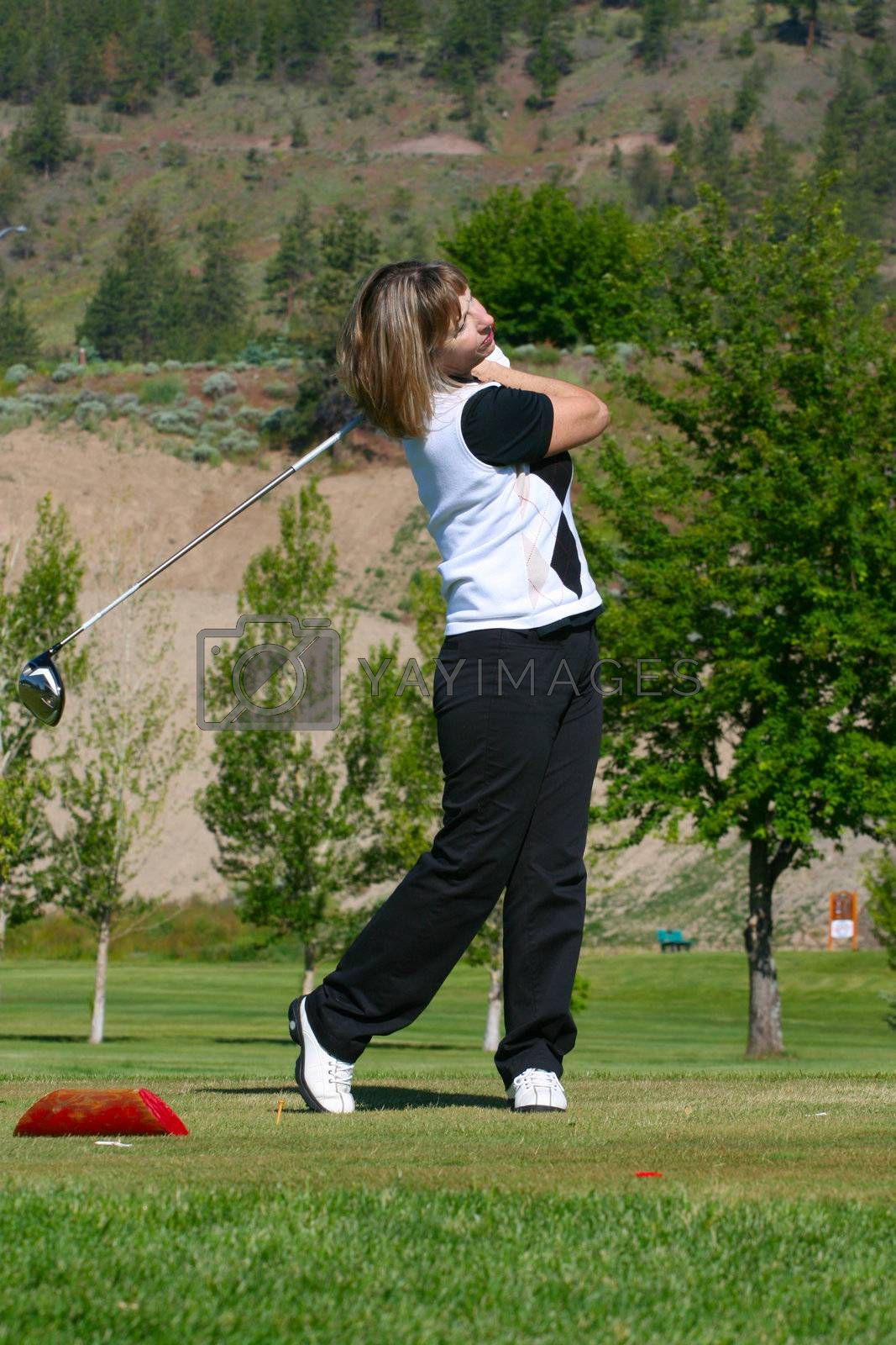 Blond female golfer following her ball from the tee-box