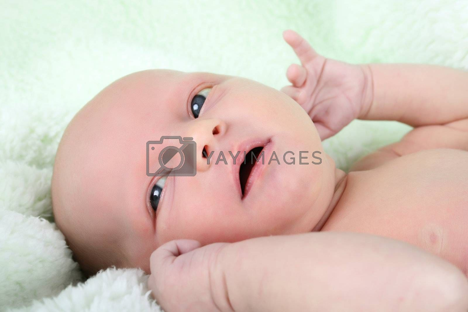 Beautiful newborn baby girl lying on a soft green blanket