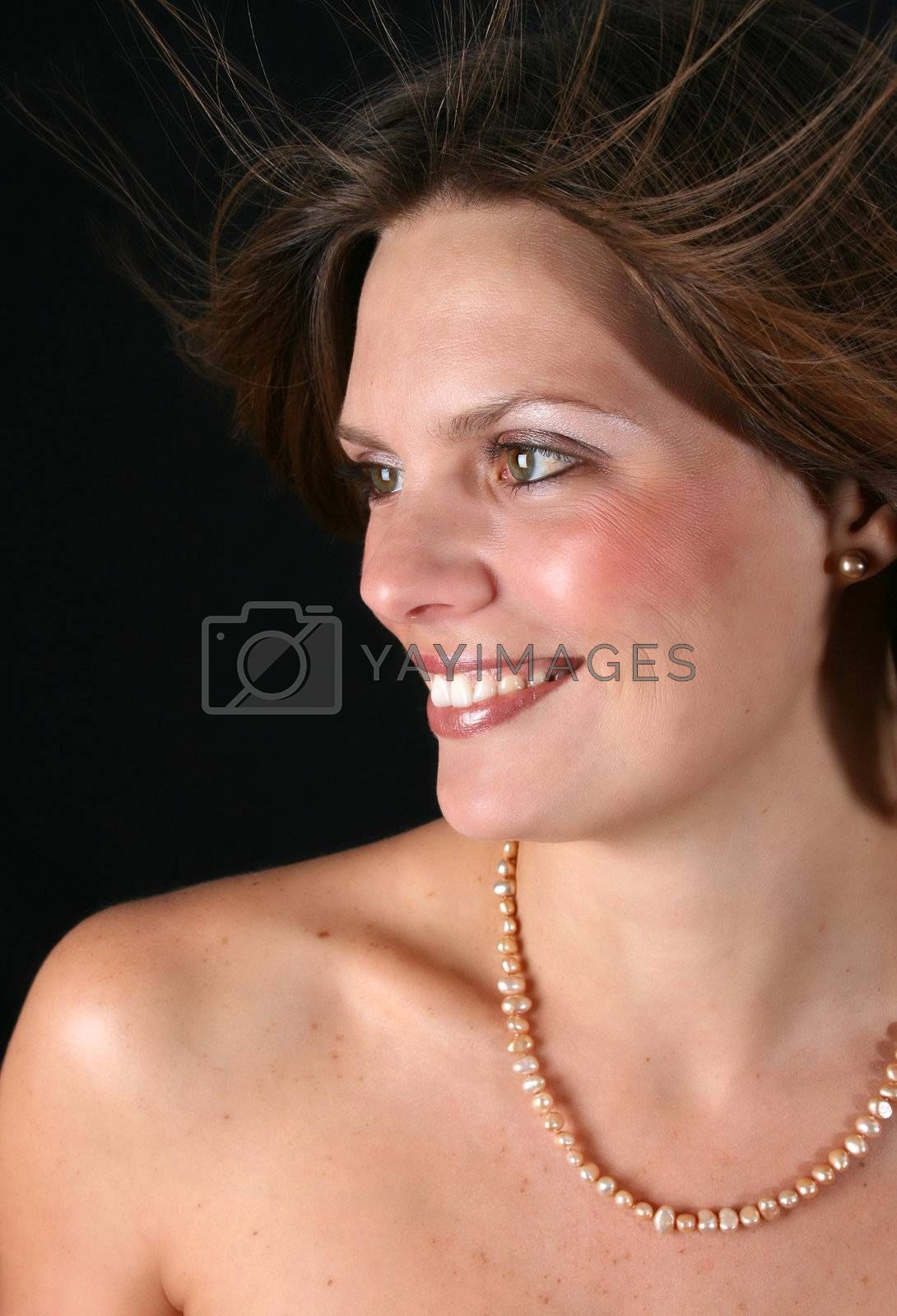 Beautiful young woman with naked shoulders and pearls