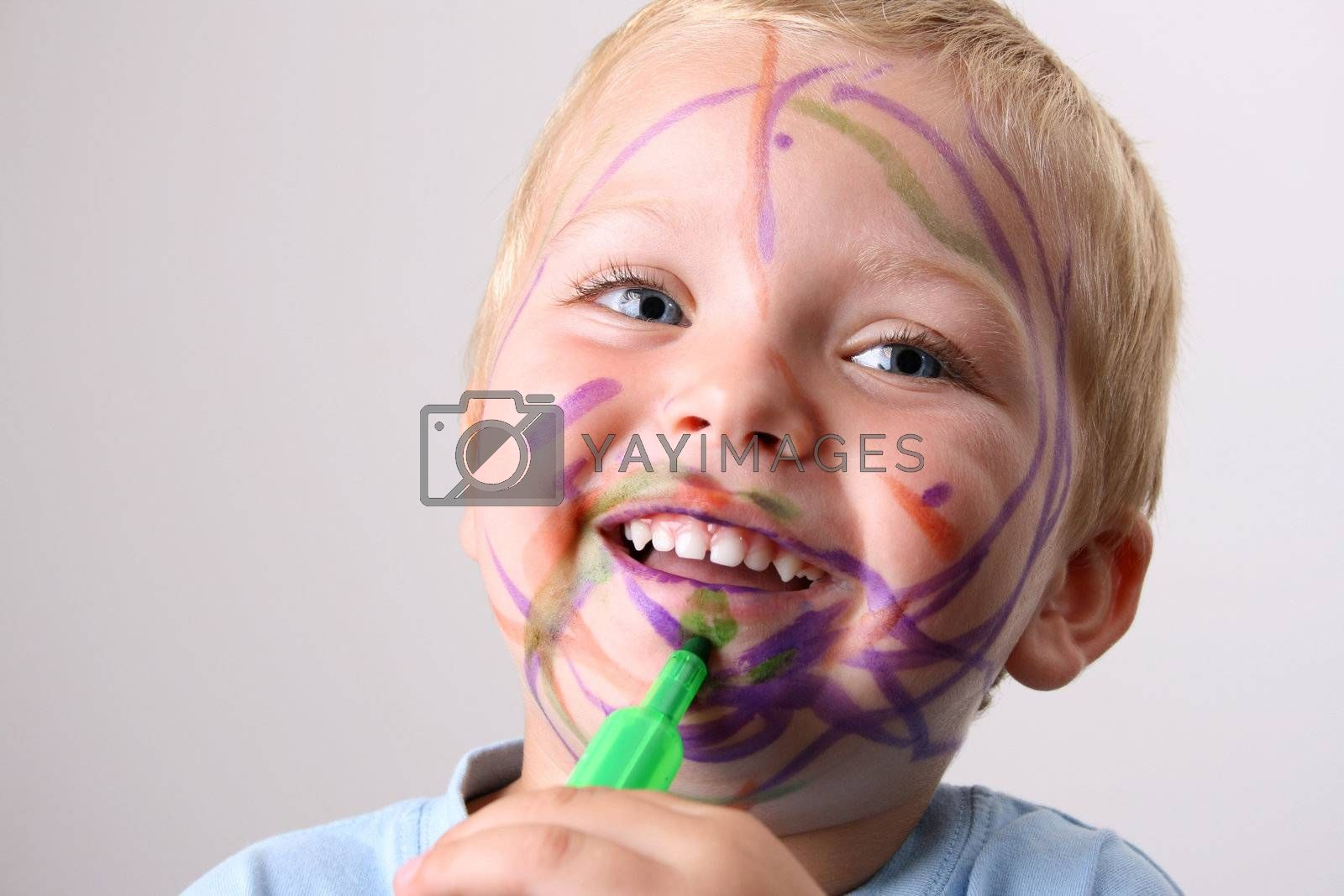 Laughing Toddler playing with colored pens making a mess