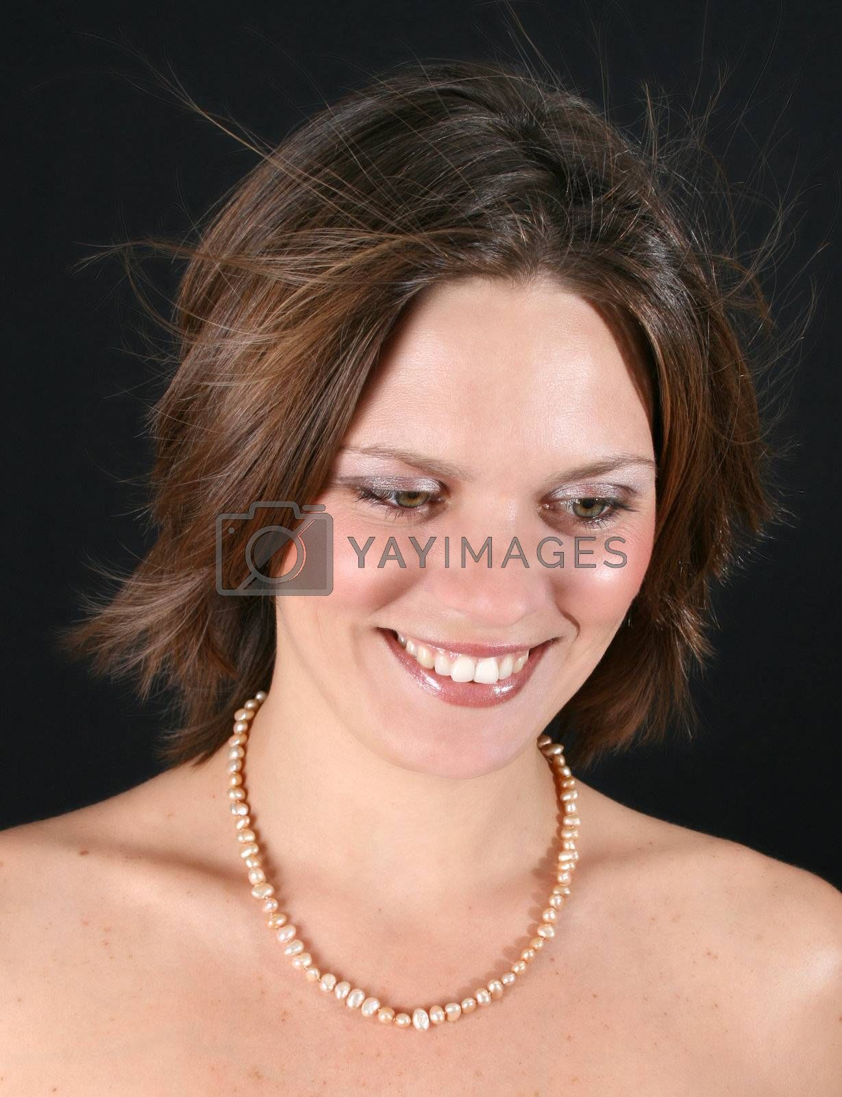 Beautiful young woman with bare shoulders and pearls