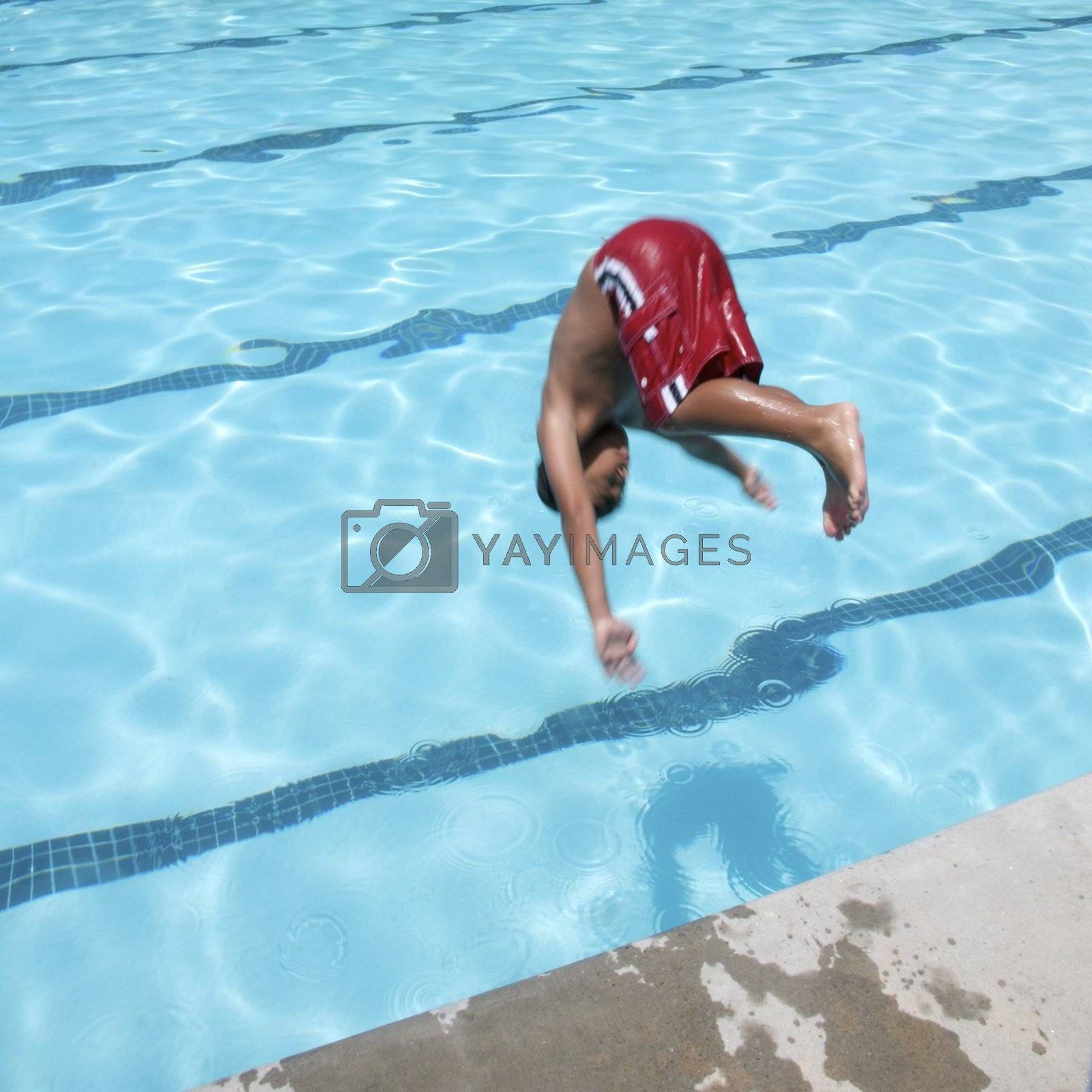 Little boy jumping into pool