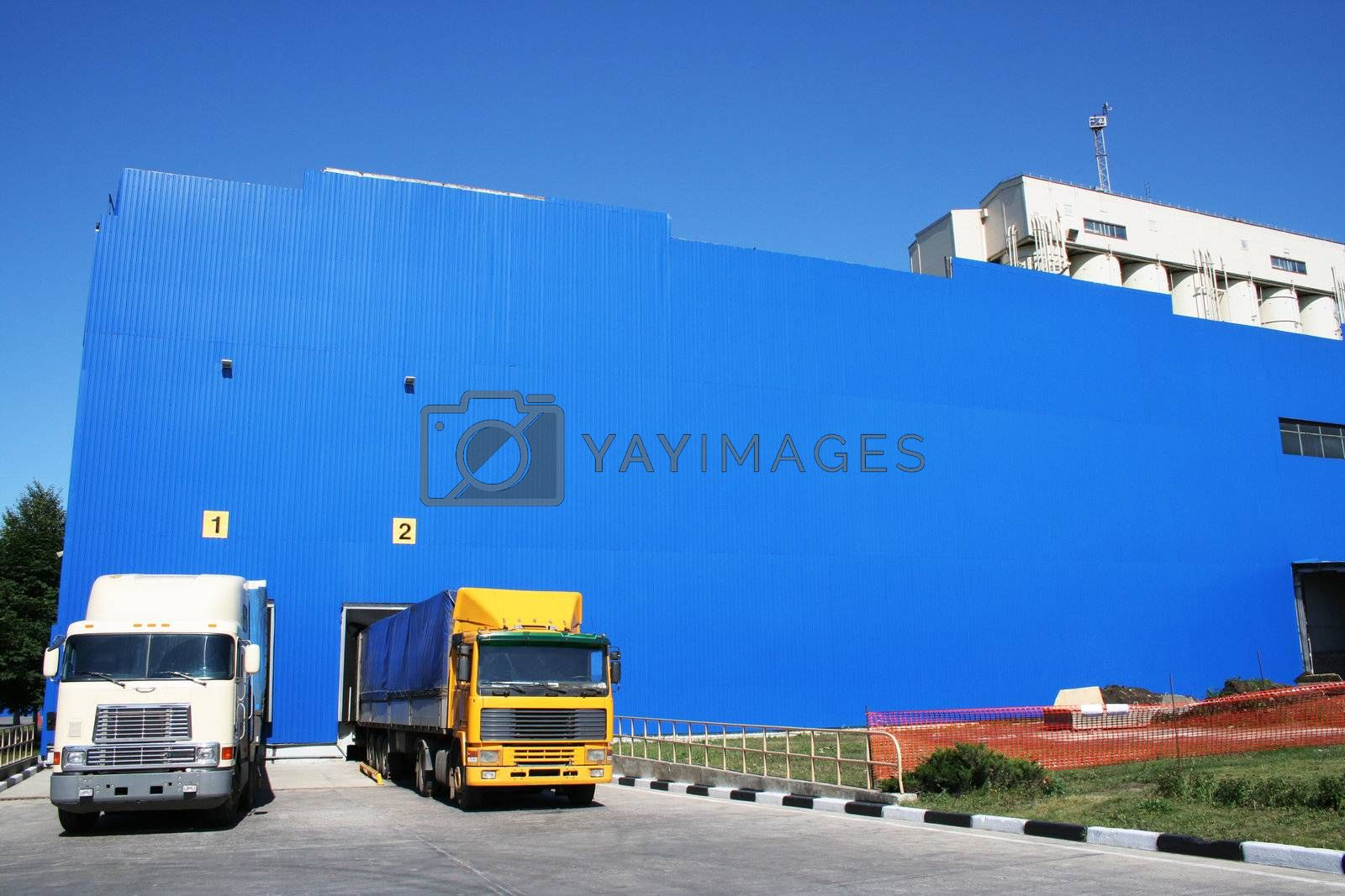 Two lorries on a background of a dark blue warehouse