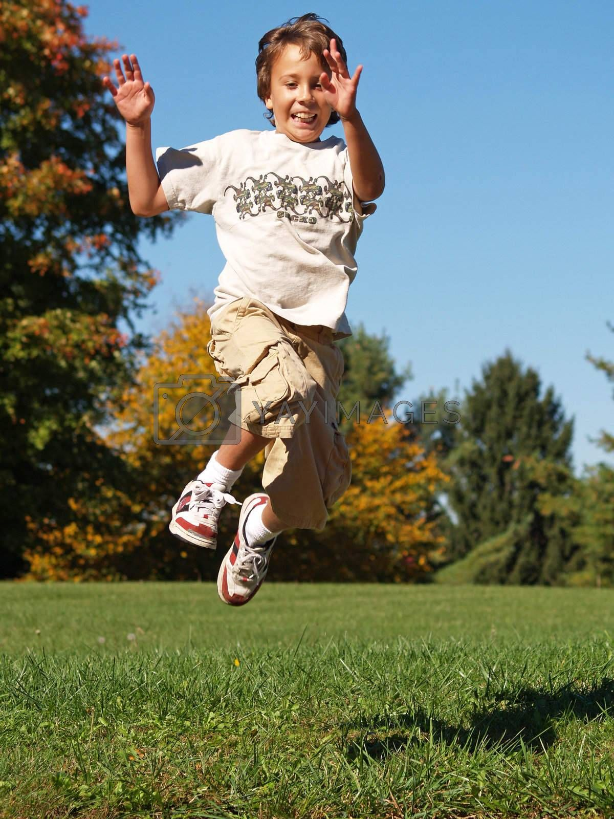 young boy jumping in the air on an autumn day