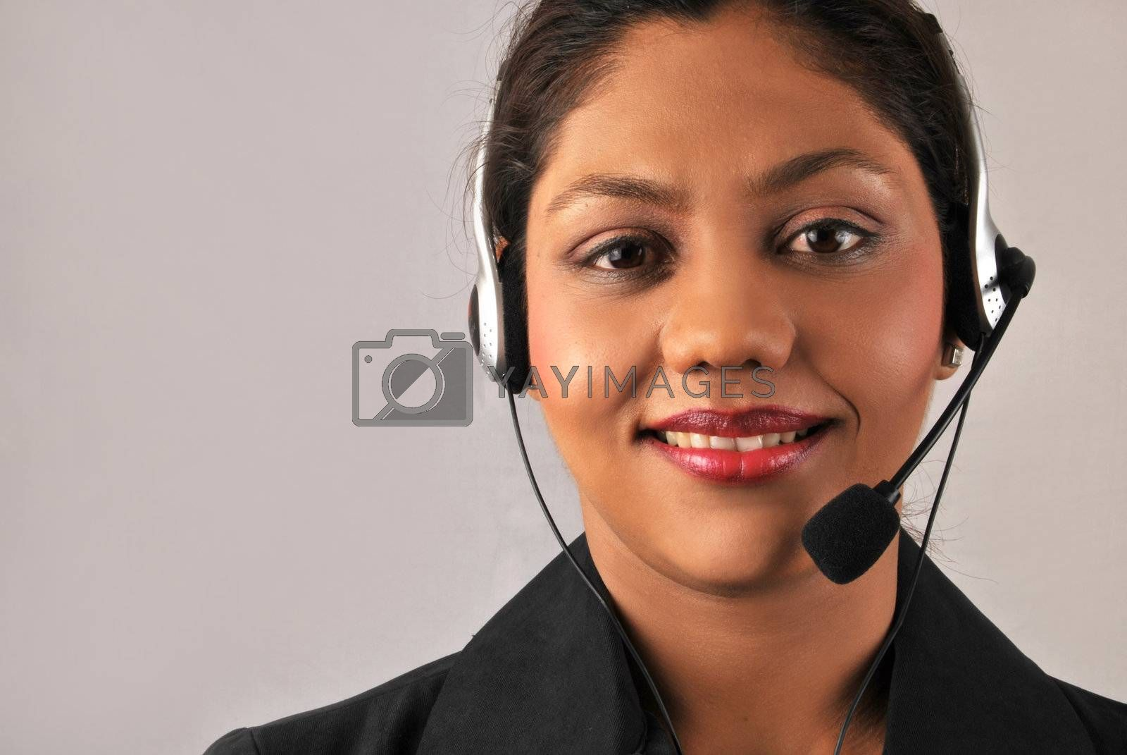 Smiling young Indian agent woman of a call center. Isolated over grey background with copy-space.