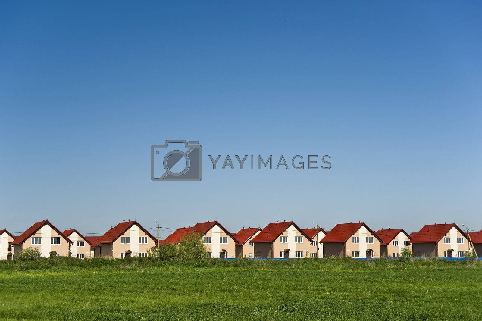 Royalty free image of New cottages and blue sky background by mulden