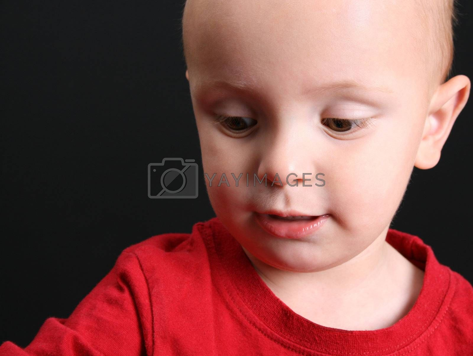 Blond toddler against a black background with a serious expression