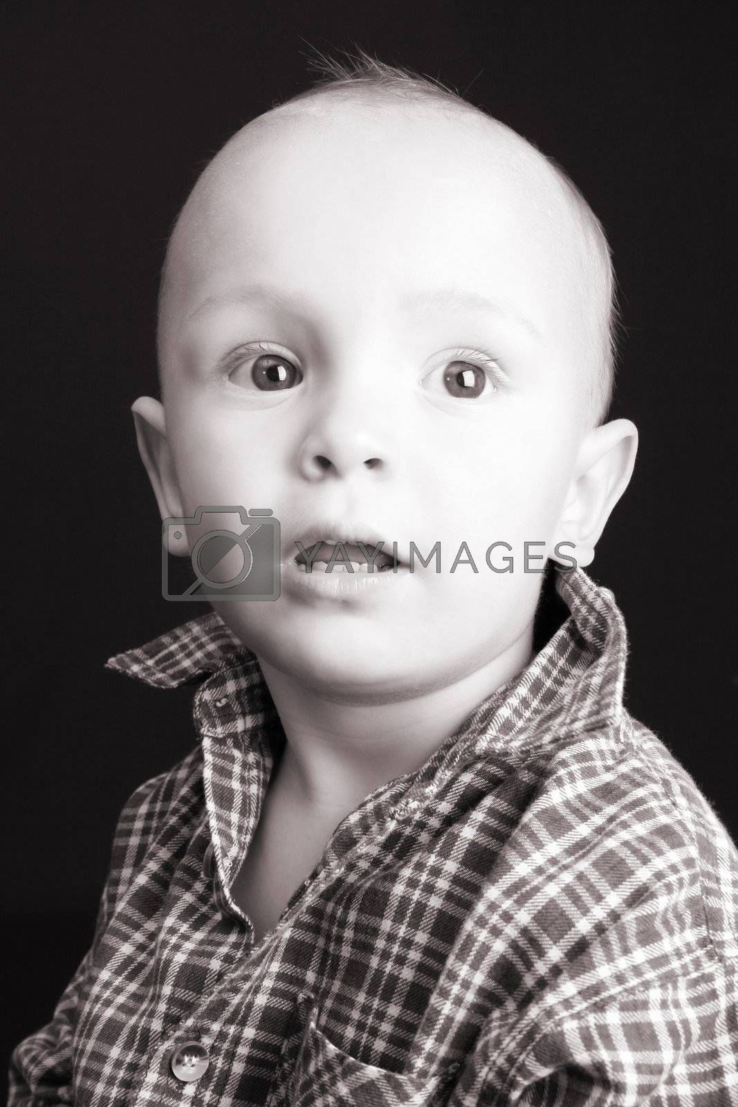 Serious blond toddler against a black background