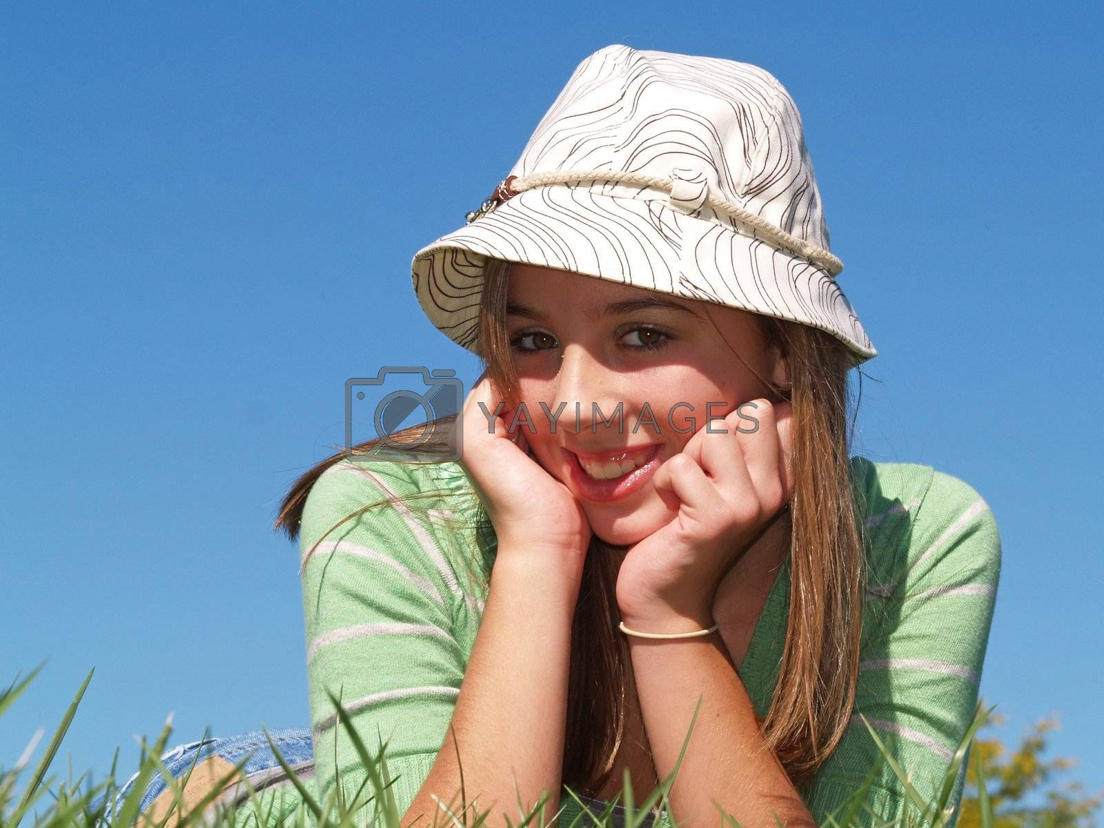 teenage girl laying in the grass with a hat