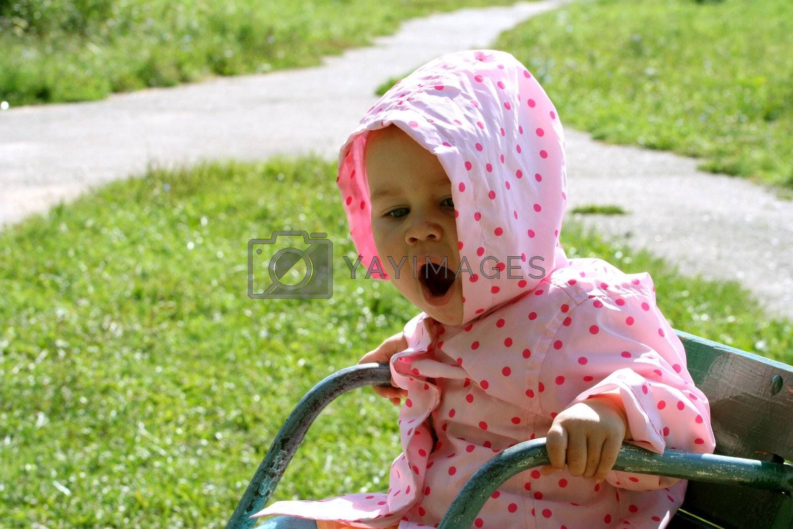 Little baby sitting on the carousel and yawning. There is green grass and crossroad on the backstage