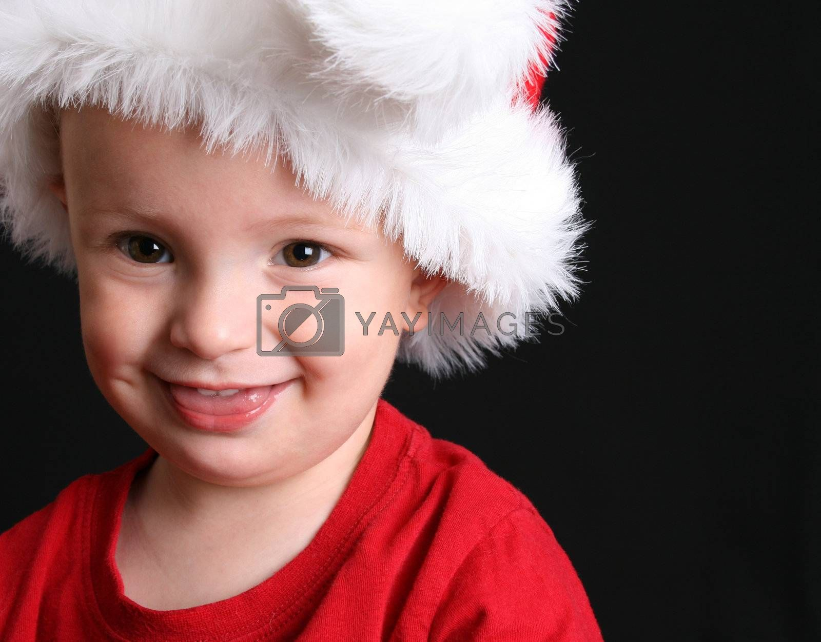Blonde toddler against a black background wearing a christmas hat