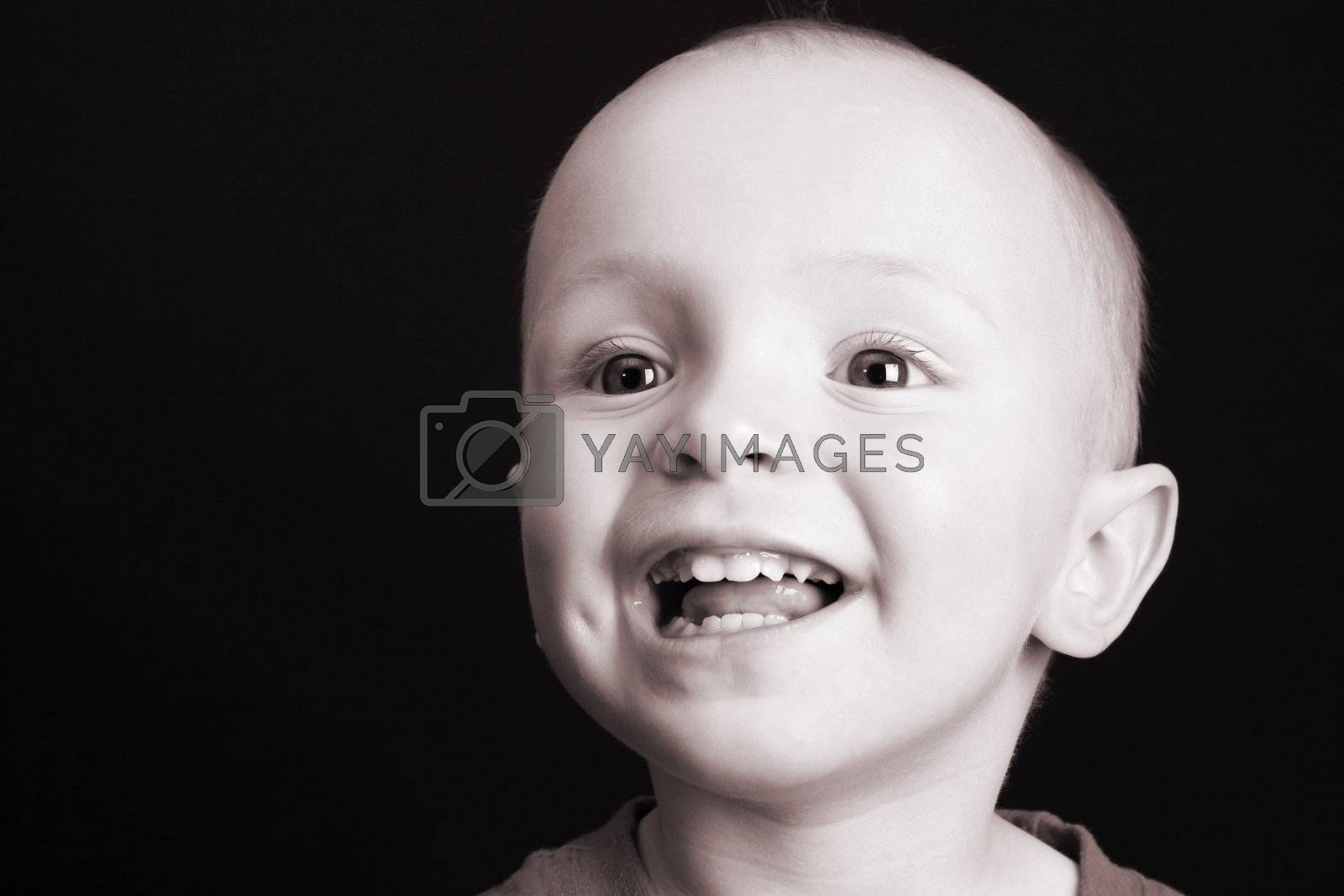 Blonde toddler against a black background with a big smile