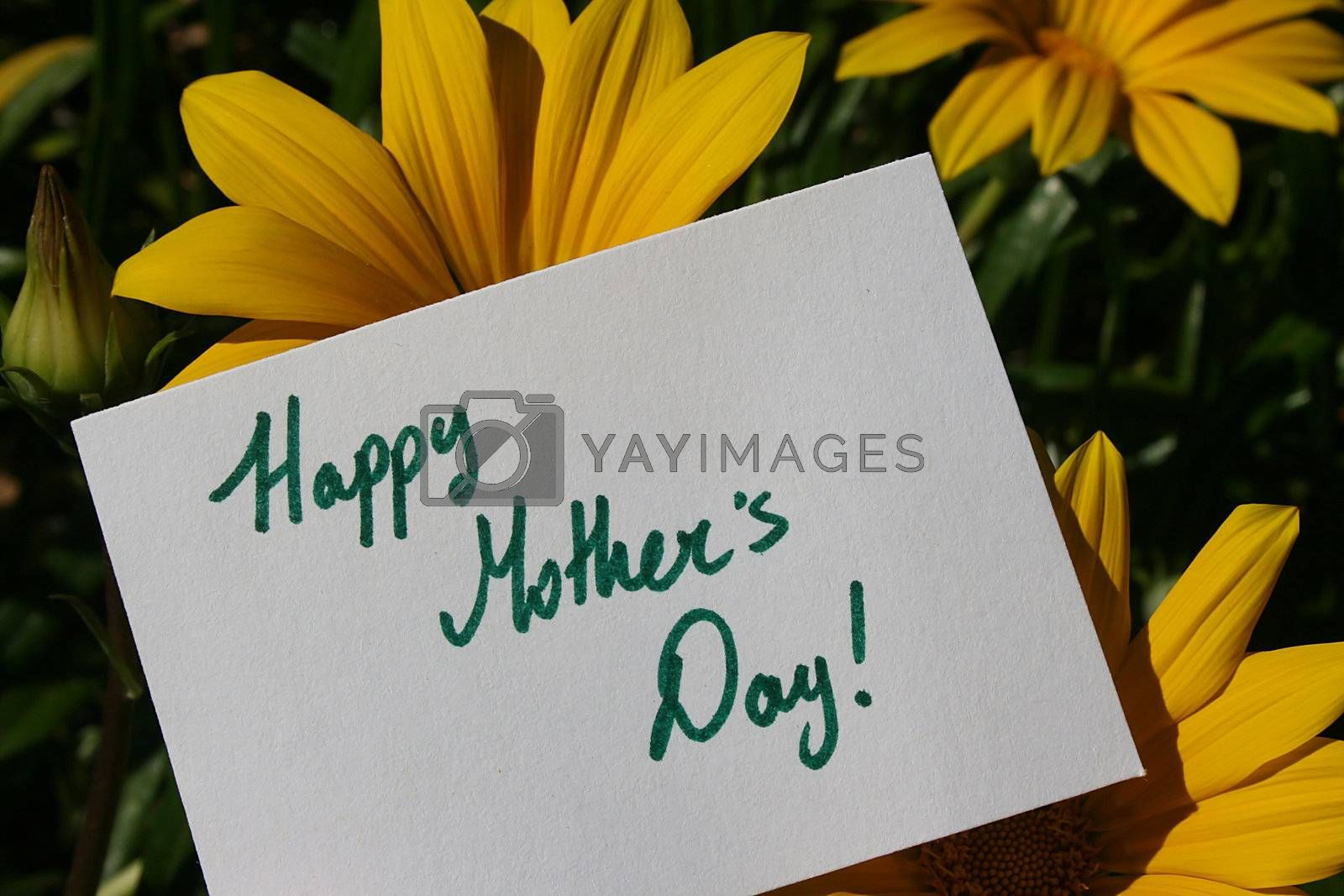 Flowers with a Happy Mothers Day text on a white paper sign.