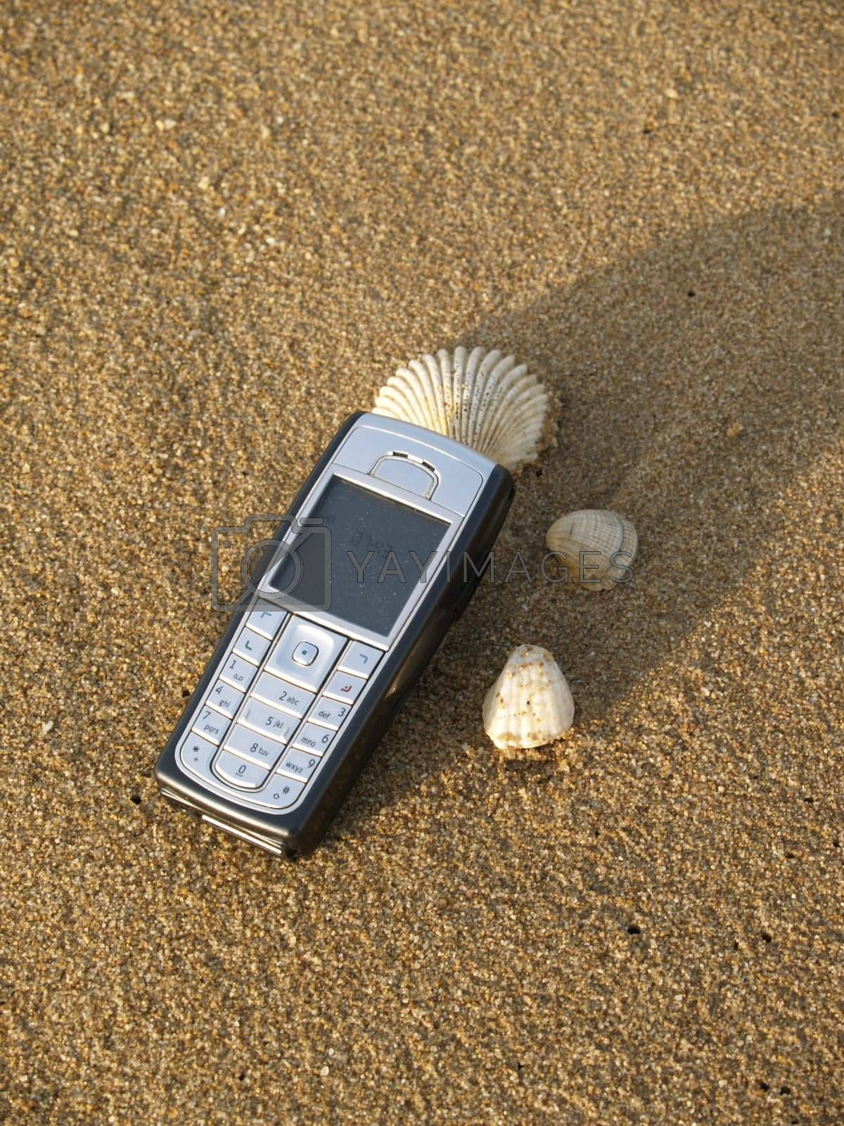 Mobile phone on the beach by epixx