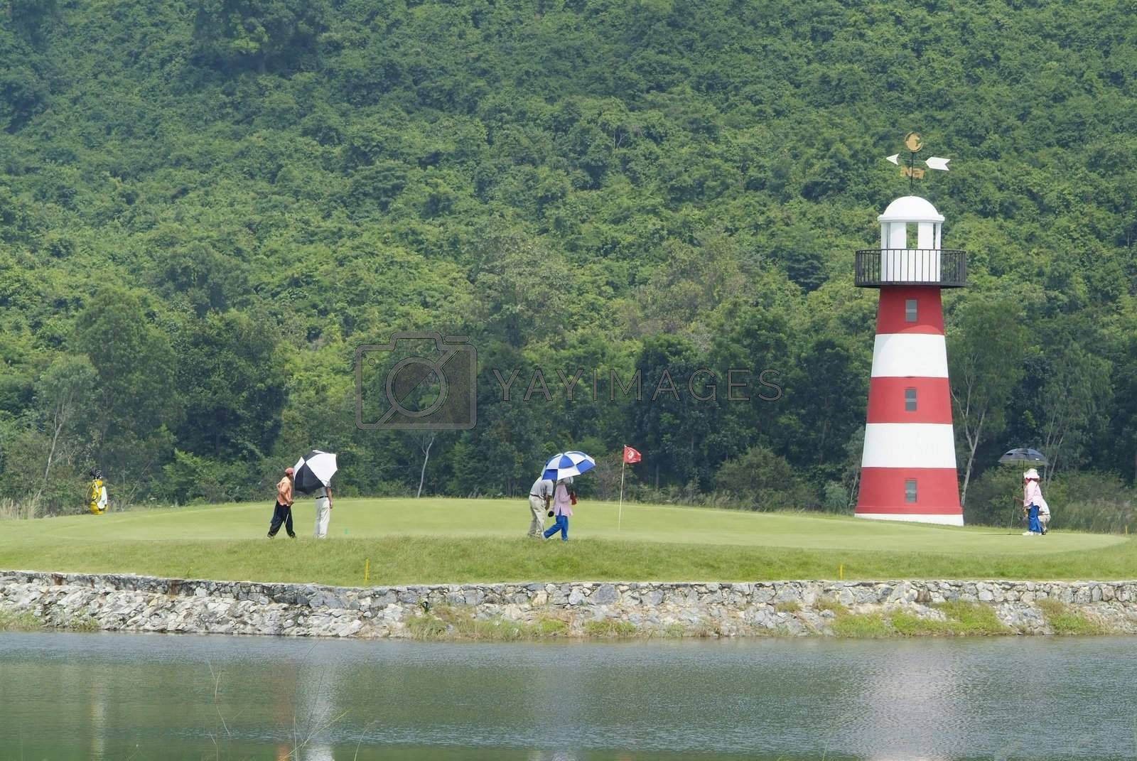Golf players and caddies on green by epixx