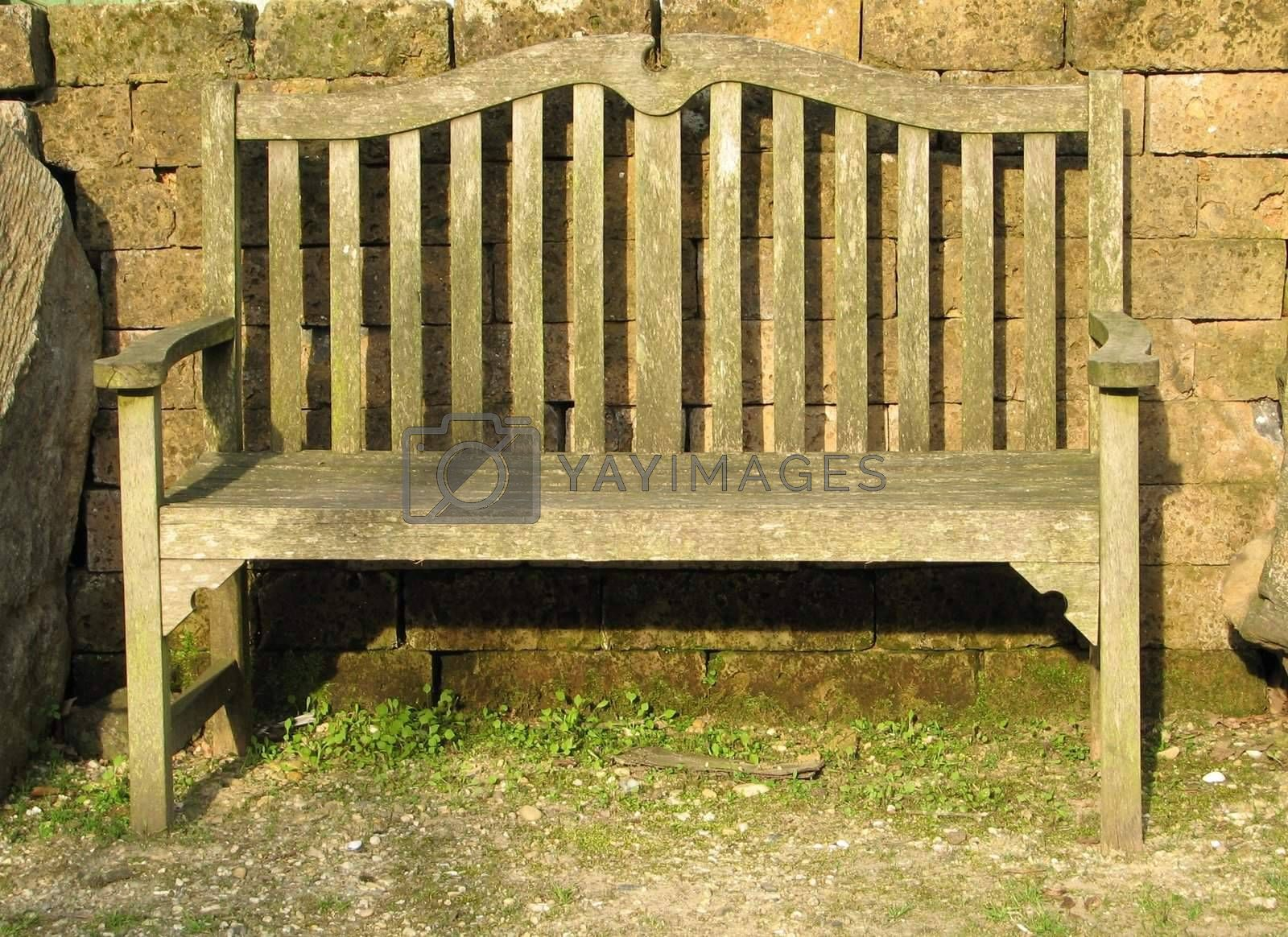 wooden garden bench in front of a stone wall