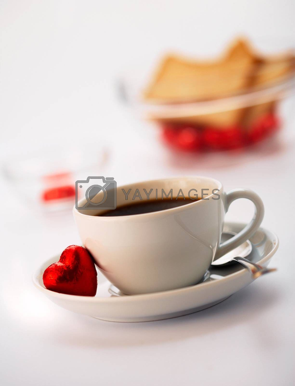 White cup with coffee and one chocolate