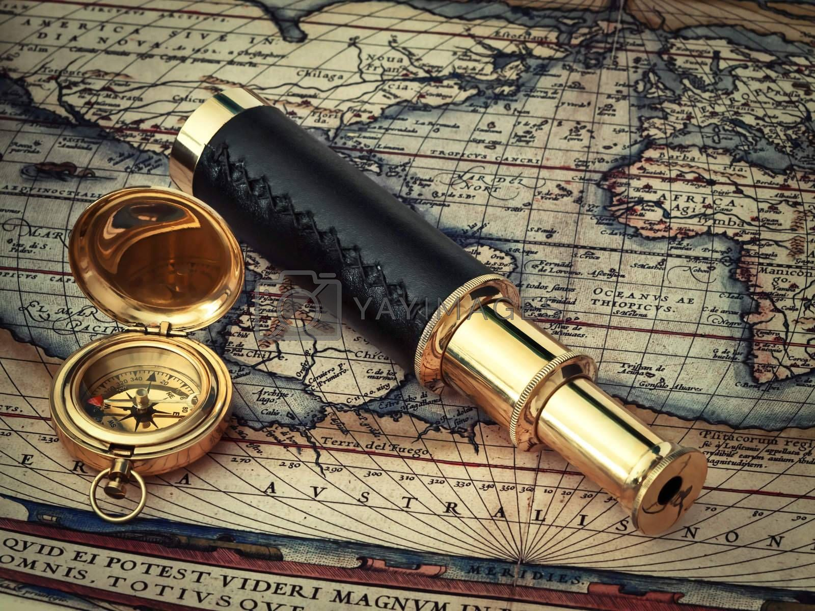 traveling theme: vintage telescope and compass at antique (17 century) map