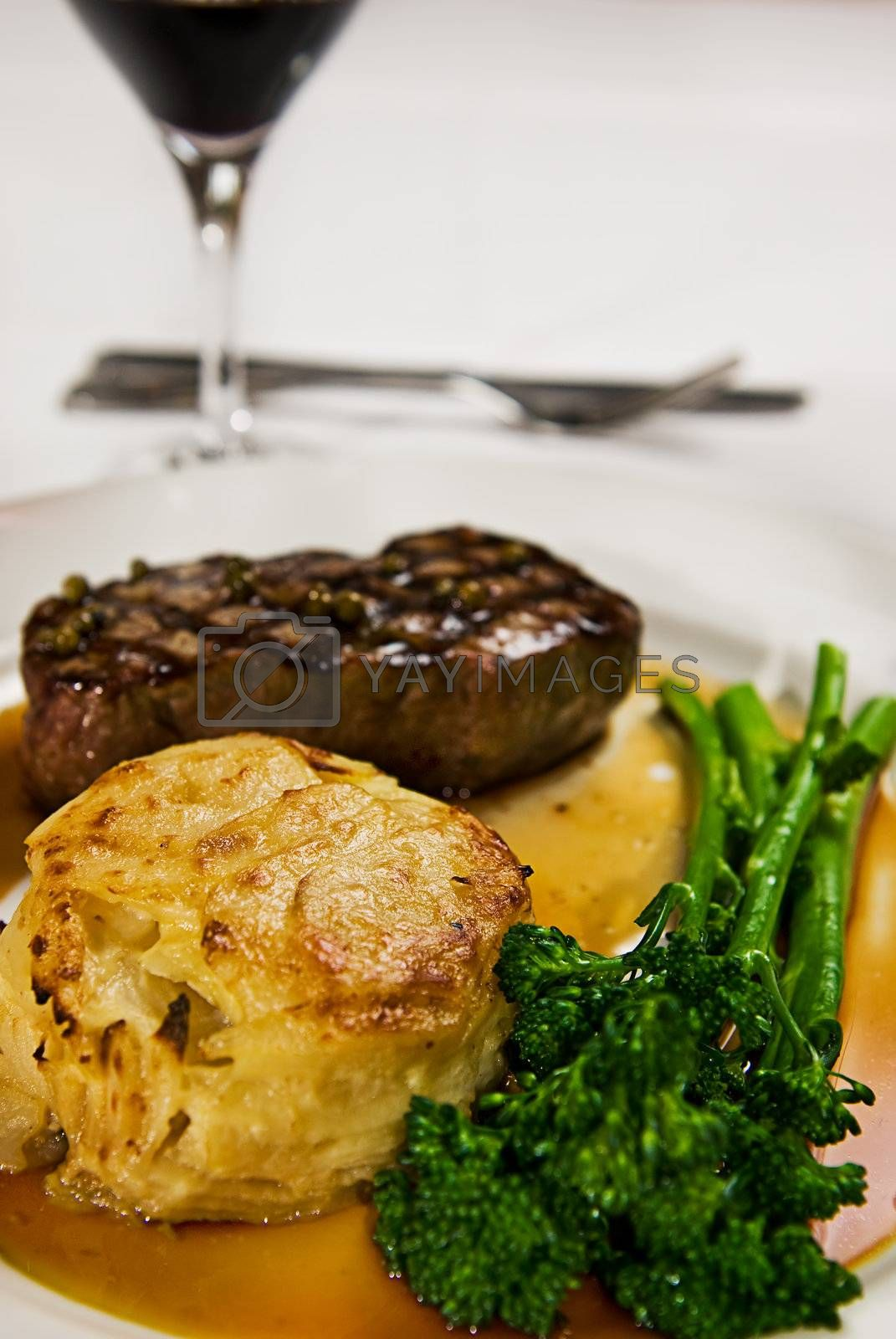 A perfectly grilled steak served with broccolini and a potato cake with gravy and red wine.