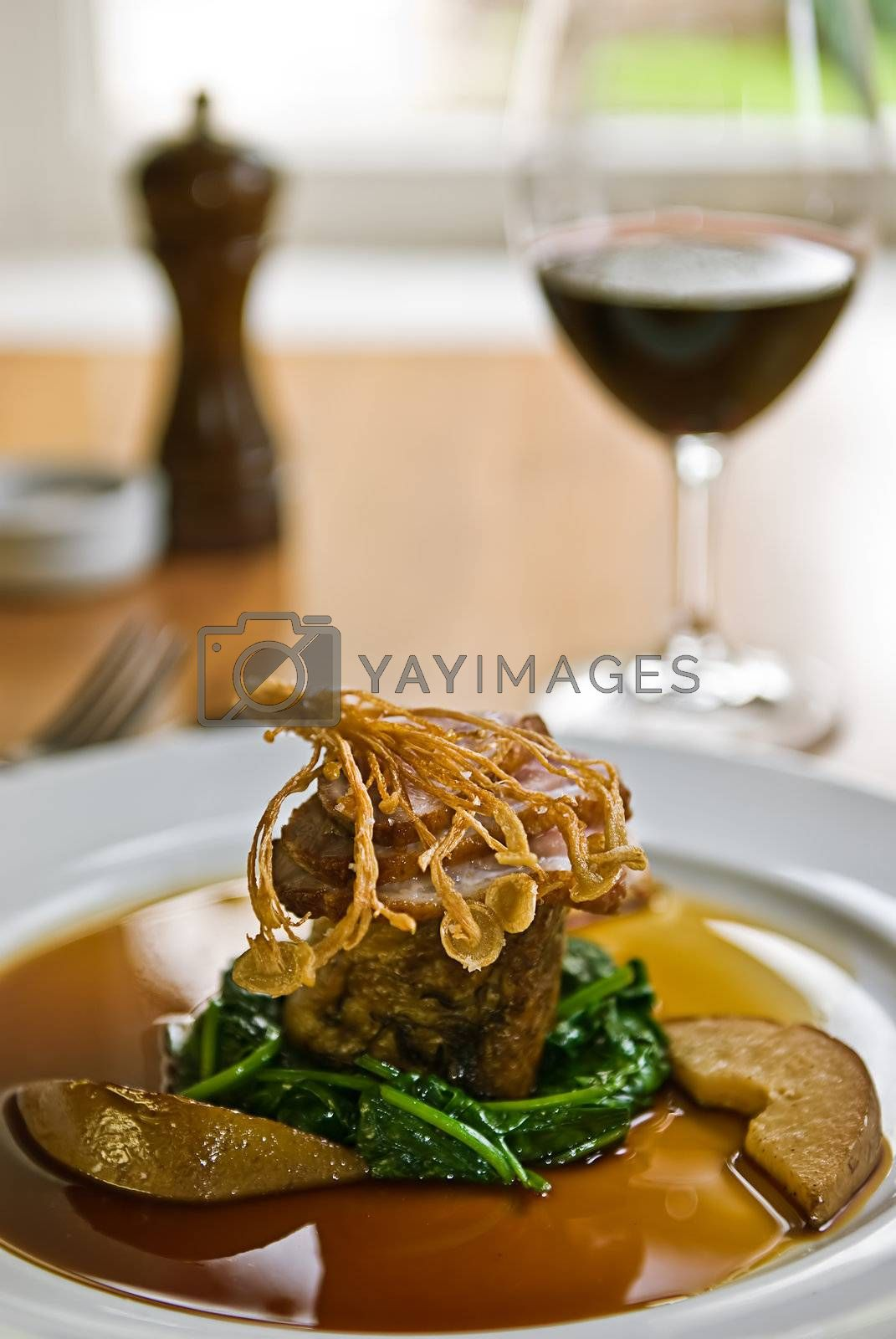 Crispy duck on a bed of spinach served with red wine in a restaurant.