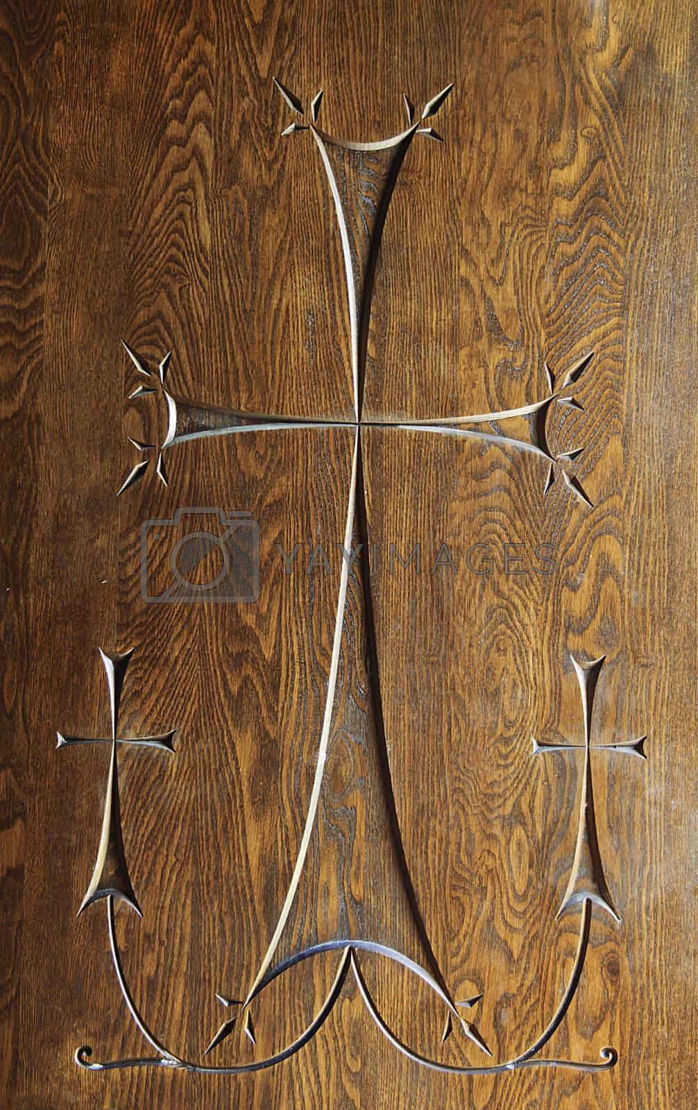 Carving of 3 cross with one large central cross joined to 2 smaller crosses on either side. Carved into an antique woodern door.