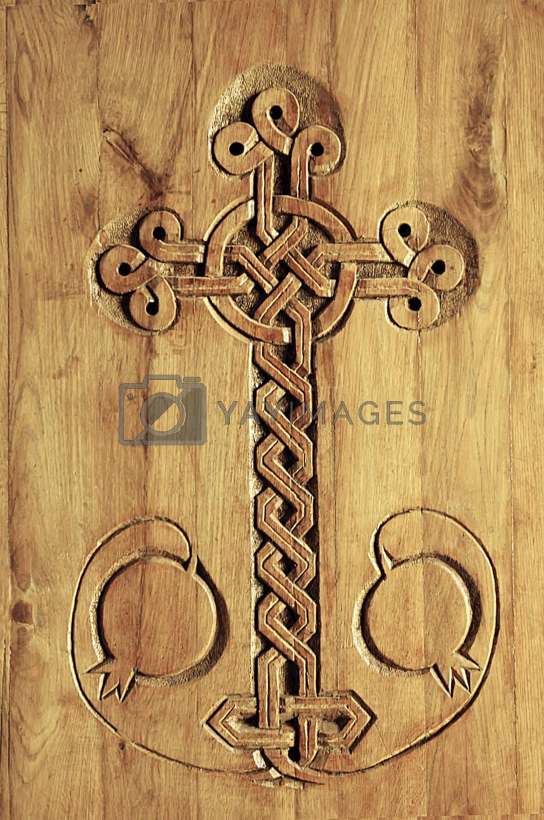 Carving of a cross in a door of an ancient Armenian Church. Carving features a intricate cross and pomegranates.