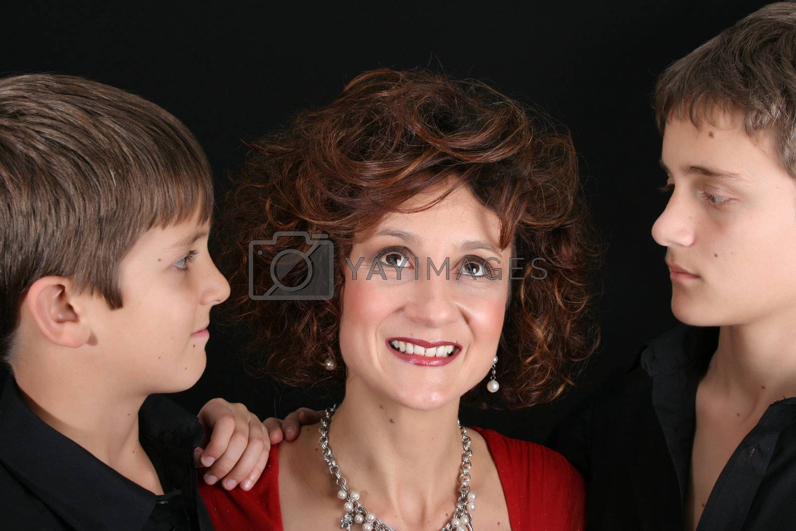 Stylish mother with her two sons on black background