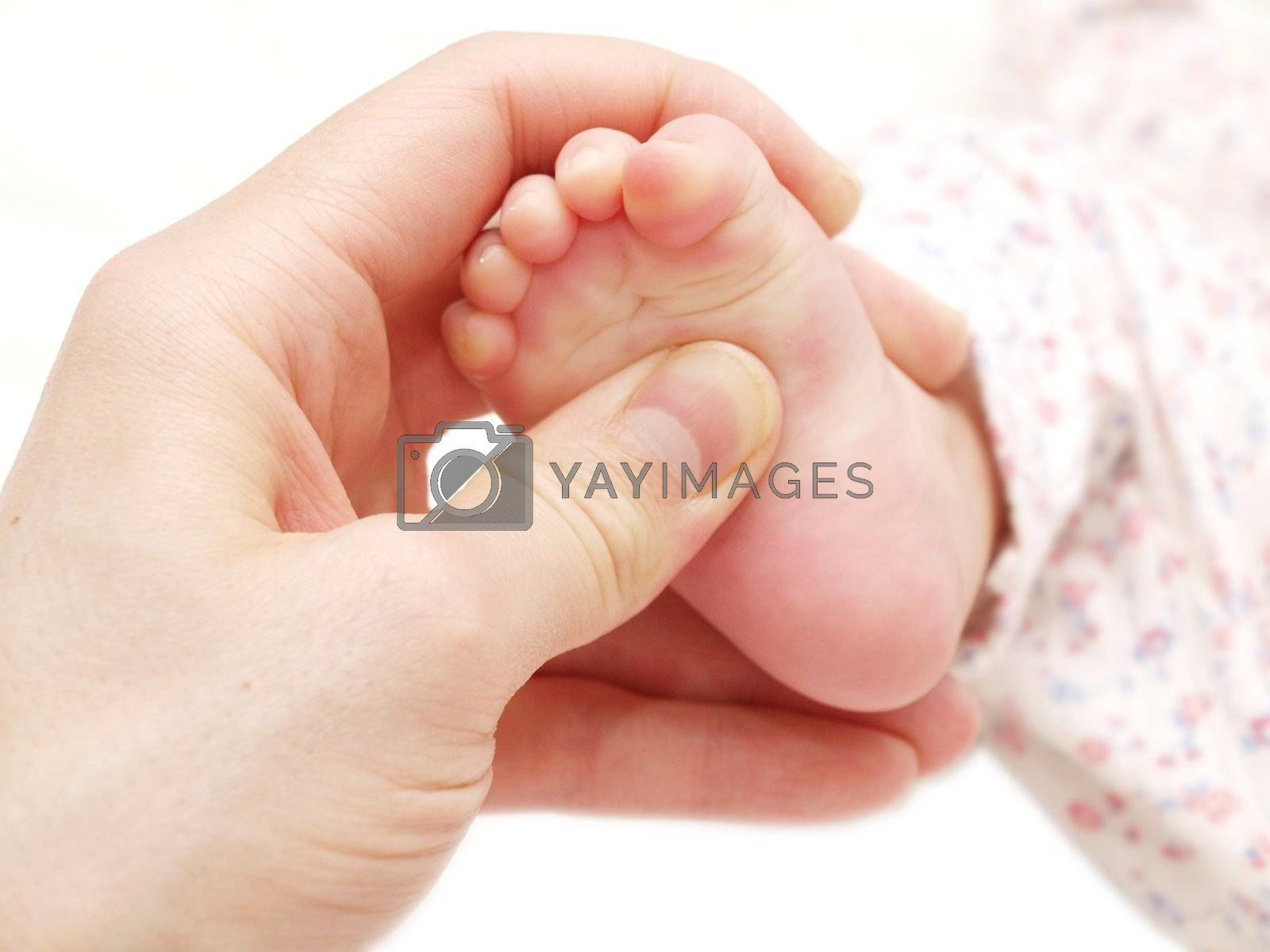 A baby receiving foot massage, towards white background