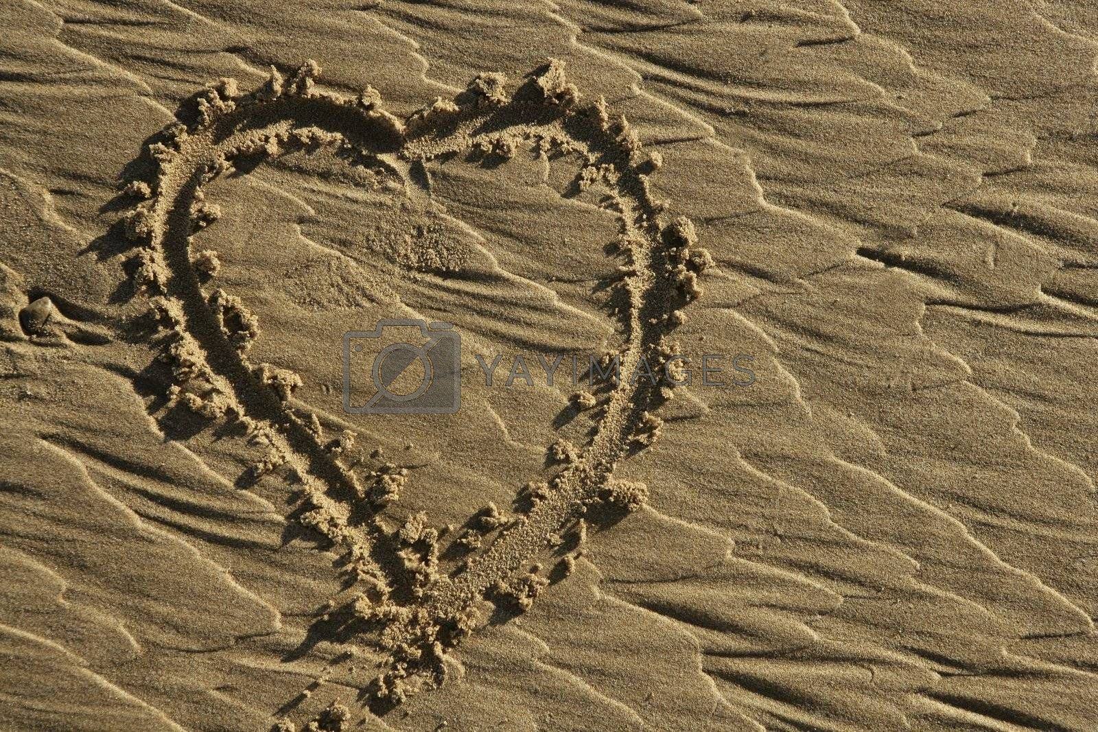 Royalty free image of hearth draw on the beach sand surface by lunamarina