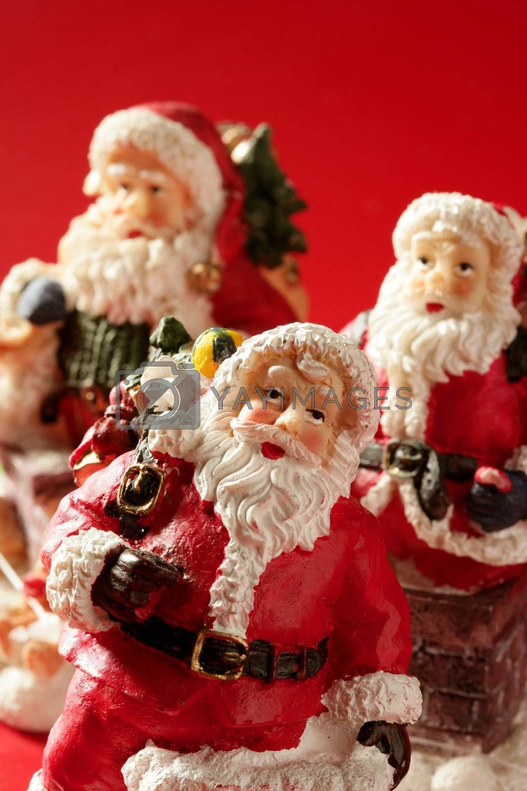 Royalty free image of Three Santa Claus figurines over red background, studio by lunamarina