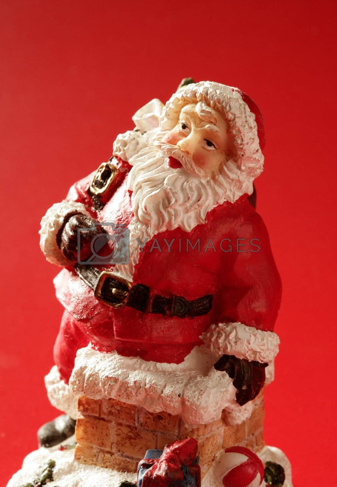 Royalty free image of Santa Claus figurine over red background, studio by lunamarina