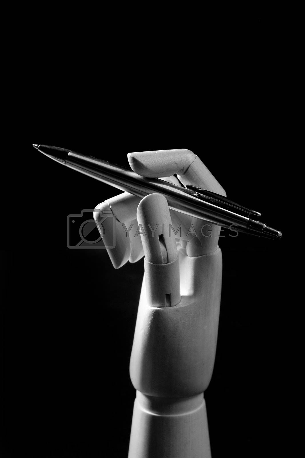 Royalty free image of Mannequin wood hand with a pen to write by lunamarina