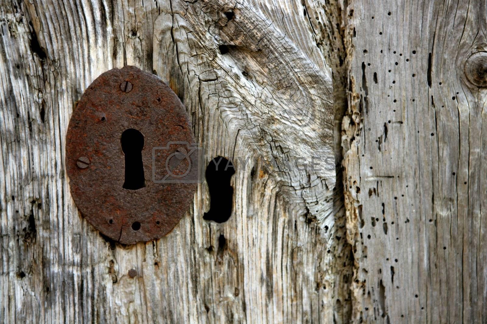 Royalty free image of Key hole over aged gray old wood by lunamarina