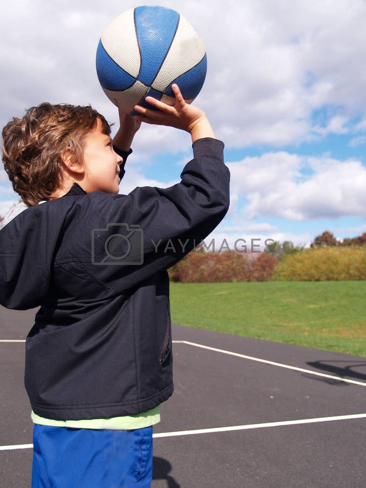 young boy attempting to shoot a basket