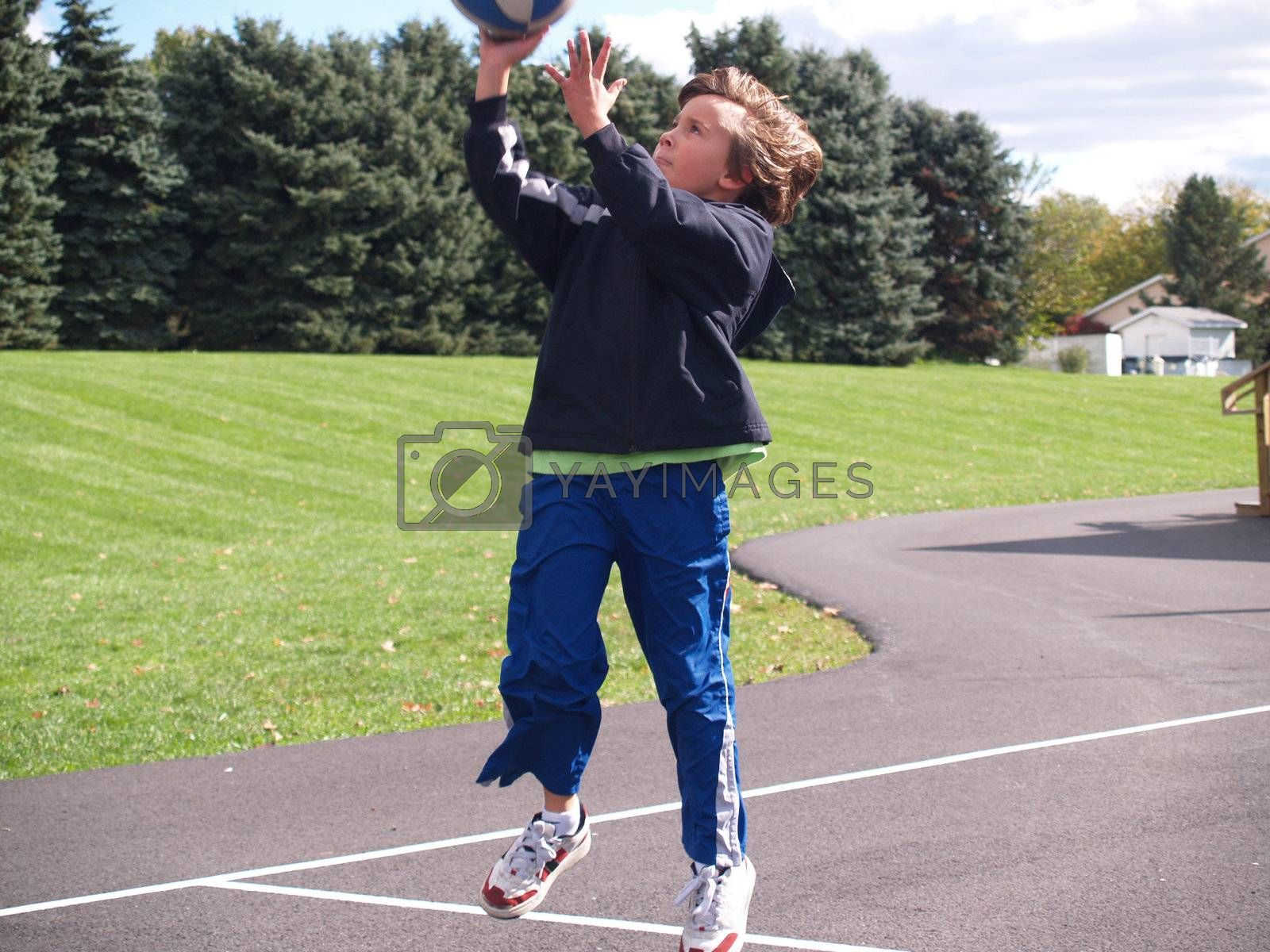 young boy throwing a basketball