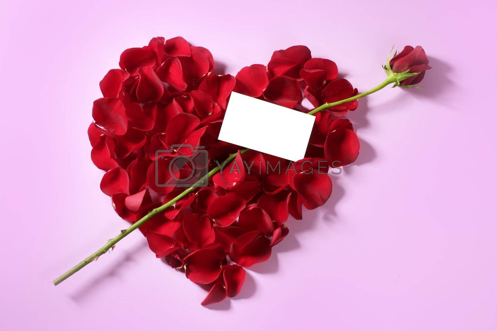 Royalty free image of Red rose petals in heart shape, copy space blank note by lunamarina