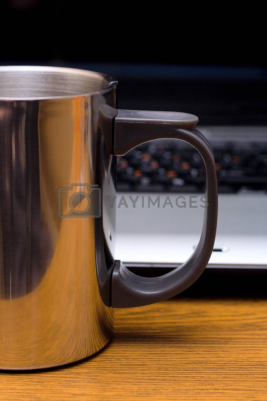 metal cup before laptop, on wooden table